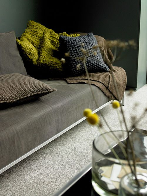 Chunky knit throws and cushions in dark colours with a touch of mustard and yellow Billy buttons make a beautiful combination.
