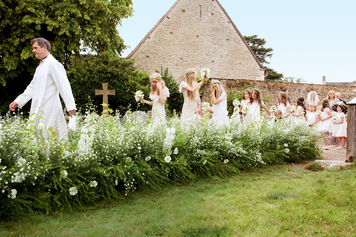 Bridesmaids and flower girls in Bonpoint proceed down the delphinium-, scabious-, and daisy-lined path to the church.