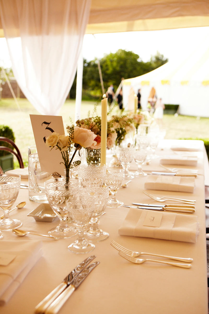 Cut crystal glasses and creamy garden roses adorn the white-on-white table settings.
