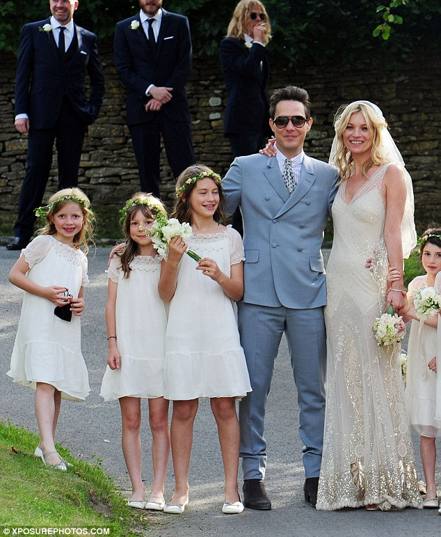 The bride wore avintage-inspired, slim-fitting, floor-lengthdress withmatching floor-length veil designer by close friend andsurpass wedding guest John Galliano. Her husbandopted for a light blue Stefano Pilati for YSL suit.