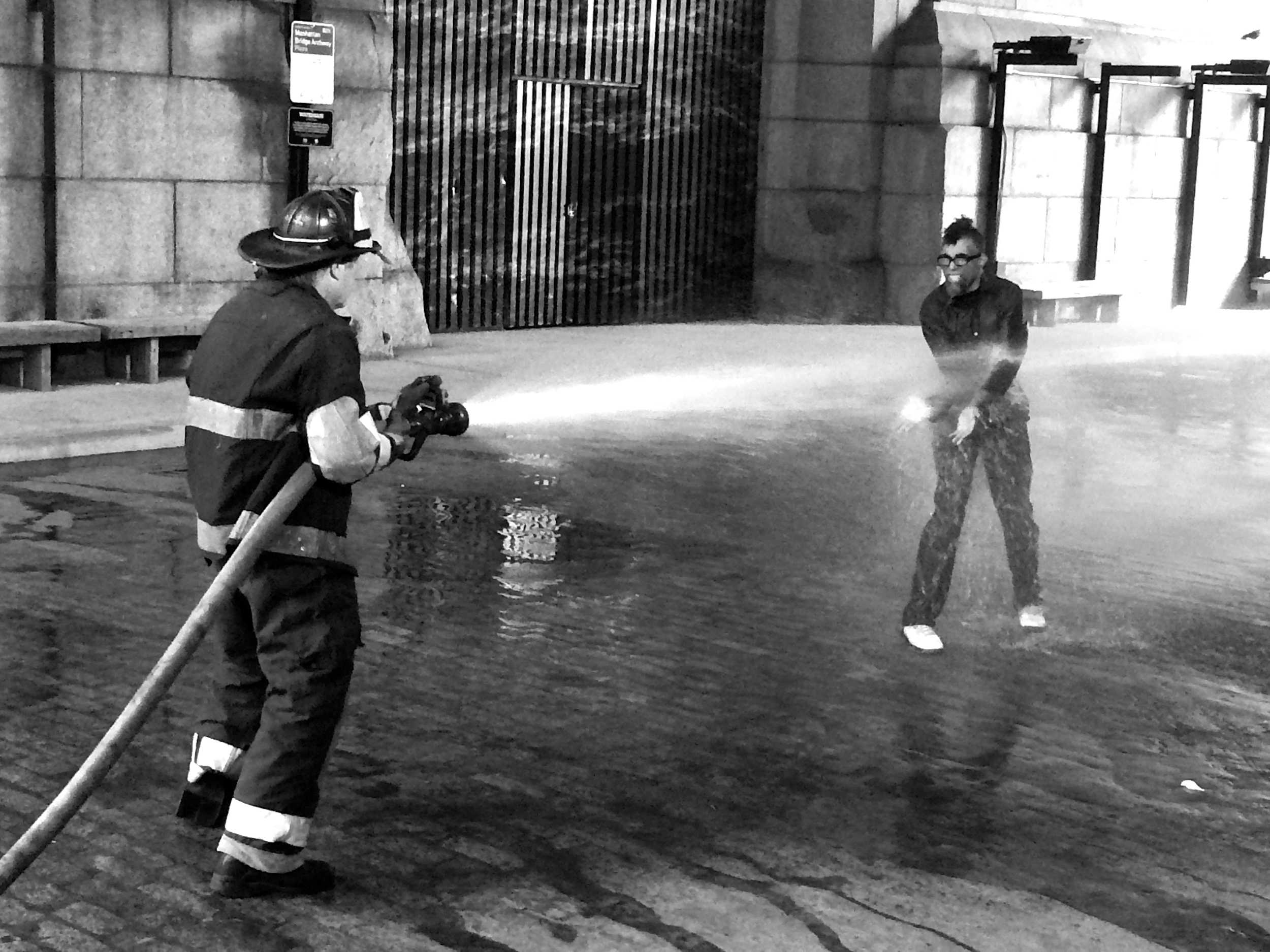 Dread Scott faces this fireman and the blast of water coming from the hose.