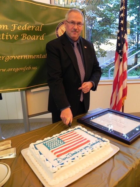 "David Ferguson, departing 2017 Chair of the Oregon Federal Executive Board of Directors, cutting the ""thank you, dave"" cake following the swearing in of the 2018 chair, Jeninifer baker (SBA). Vice Chair, tina burke (tsa) was not present."