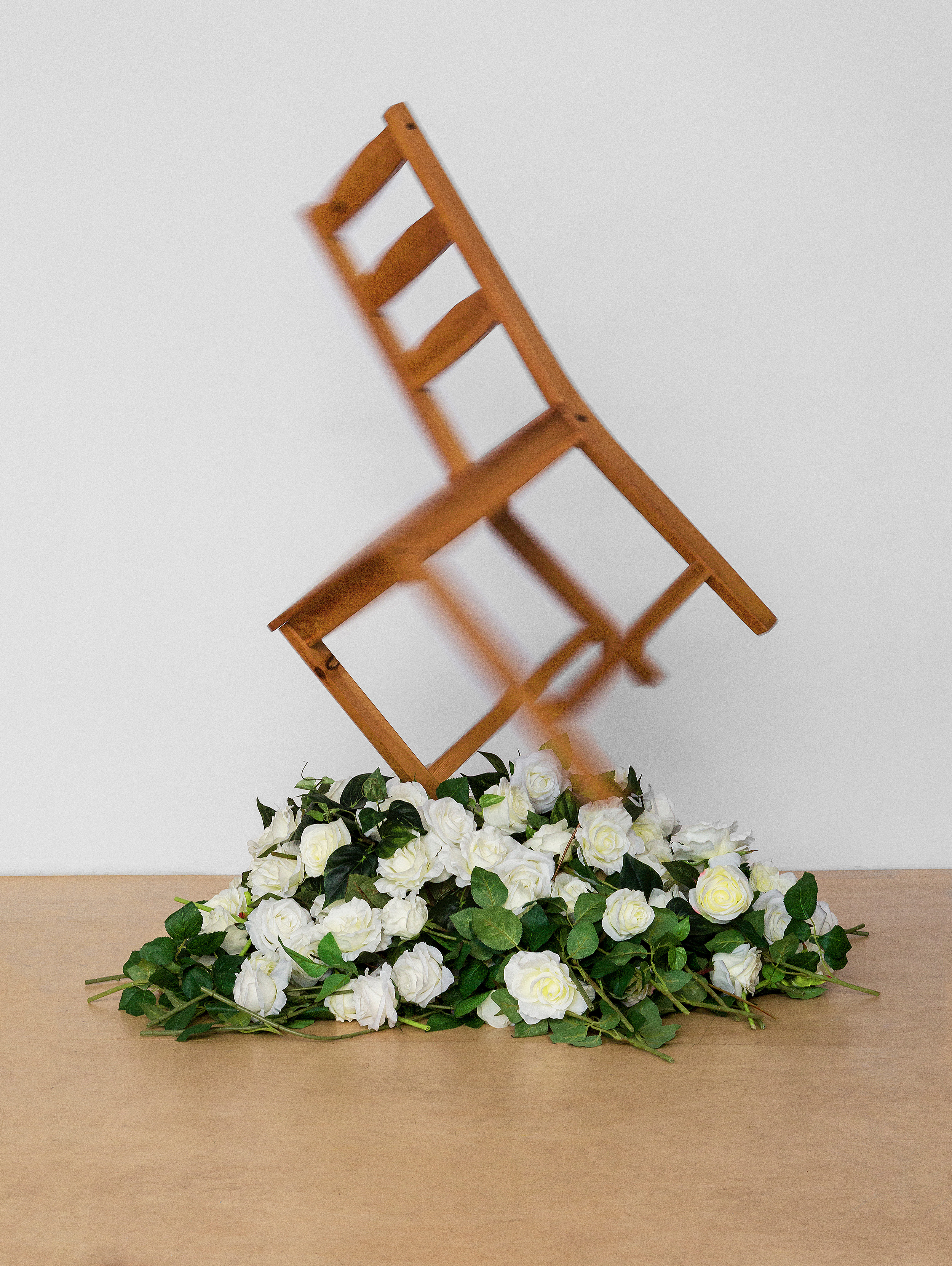 - Untitled (Follow The Leader), 2018Ikea Wooden Chair, White Roses, Motor, ElectronicsThis piece consists of a wooden chair endlessly rotating atop a bed of white roses. Evoking a subversive yet macabre scene, this piece questions the permanence and futile nature of an inanimate object through personification. Over the course of an exhibition, the live roses will wither and eventually die.Link to Video