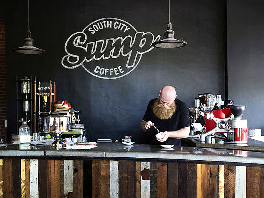 The founder and owner, Scott Carey, pouring a latte in front of the old chalk sign that was replaced this year.
