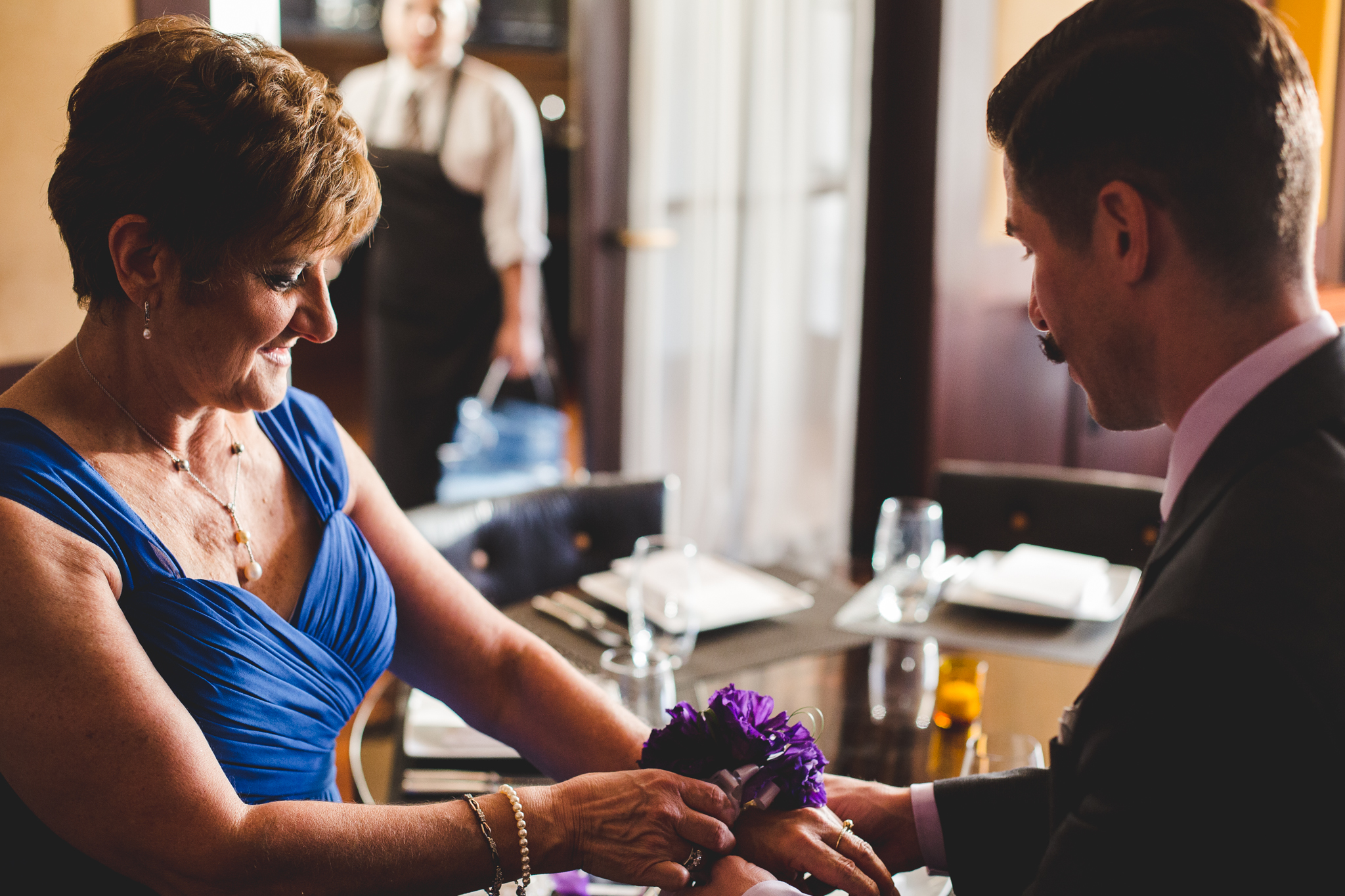 chad groom puts corsage onto mother of bride