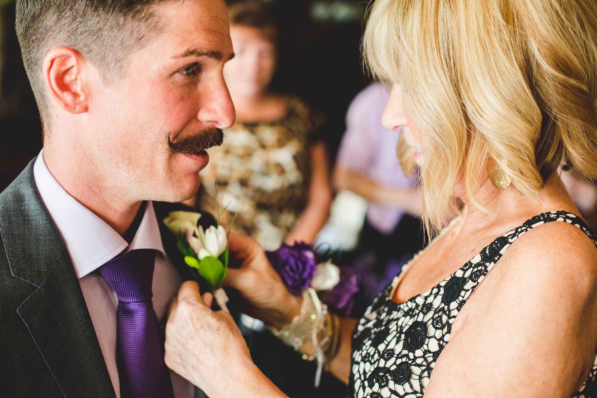groom gets boutonnière put on
