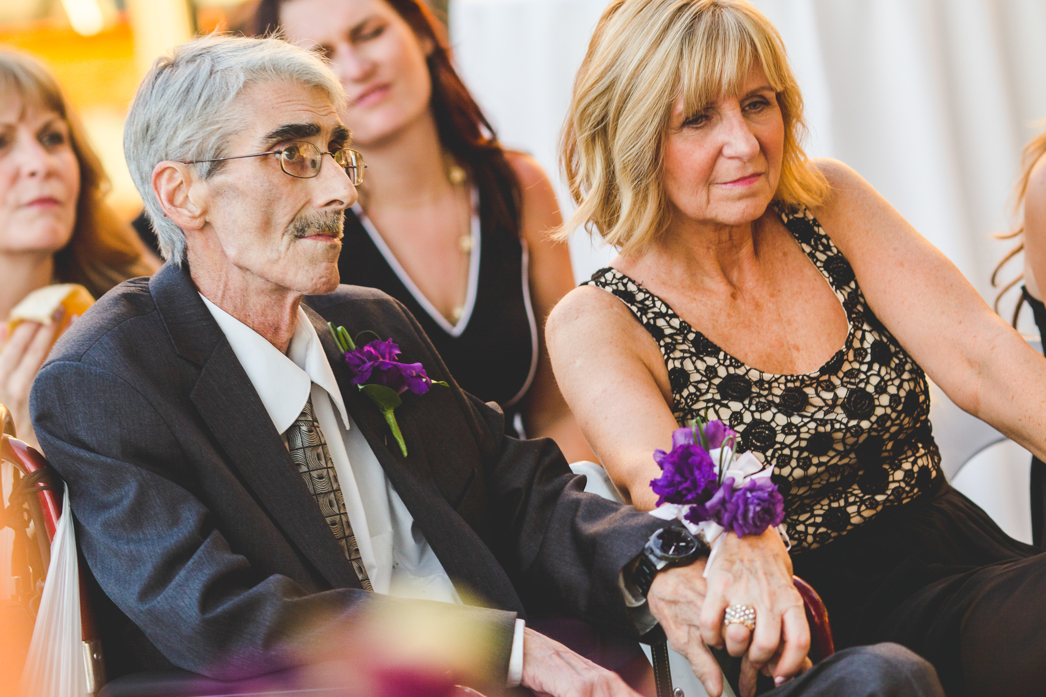 parents of groom hold hands at ceremony lc