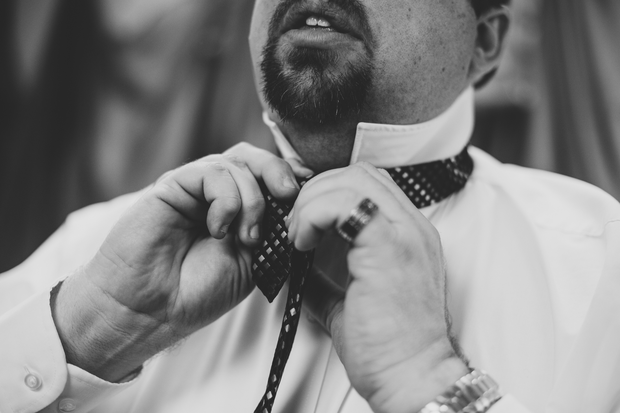 rs groom puts his tie on getting ready bw