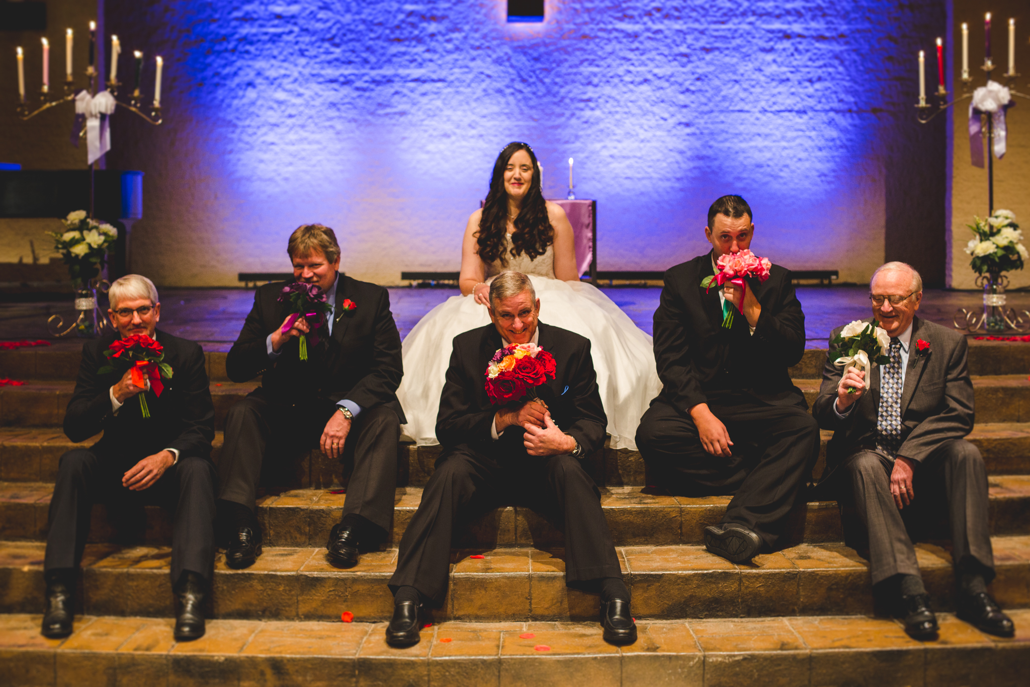 rs fun silly group shot bride men smelling bouquets