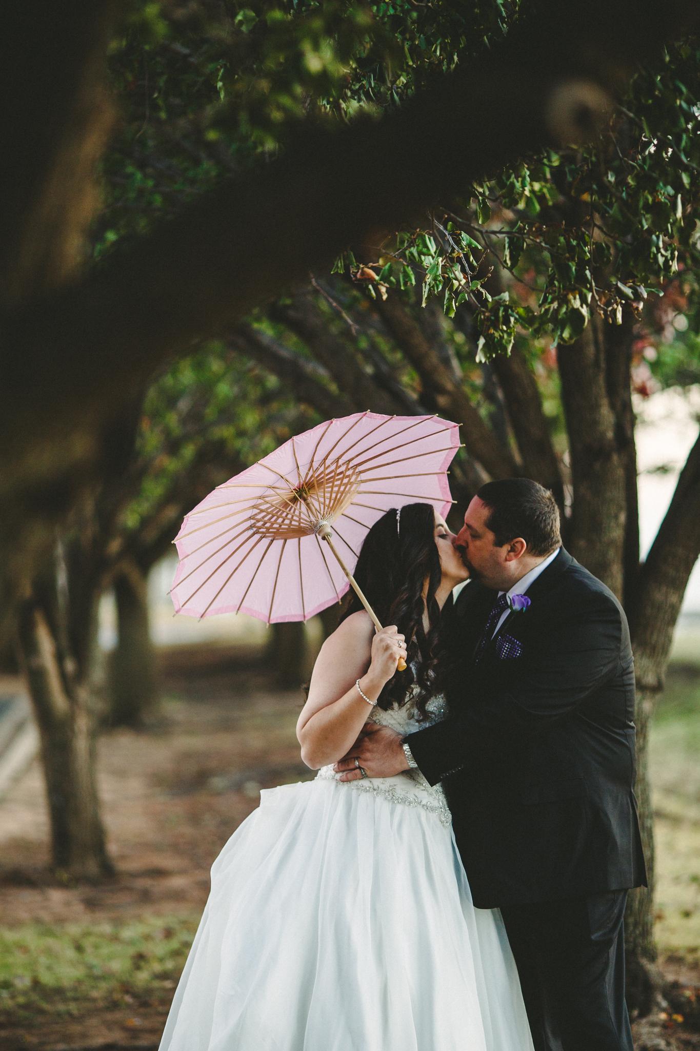 rs groom kisses bride under greenery trees oklahoma city