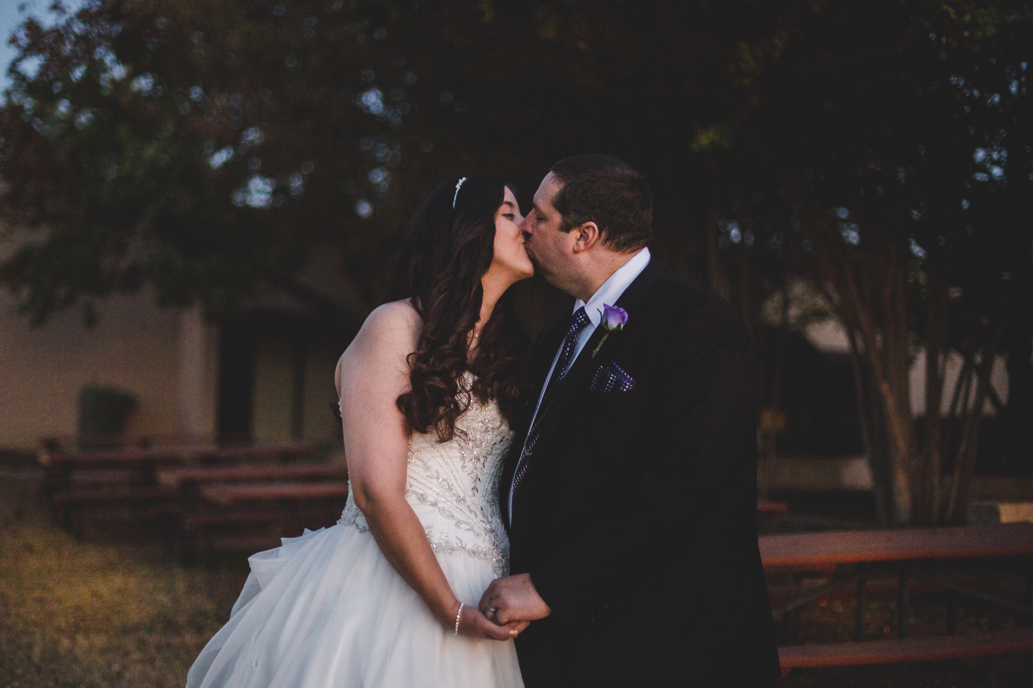 rs bride and portrait groom kiss outside at night