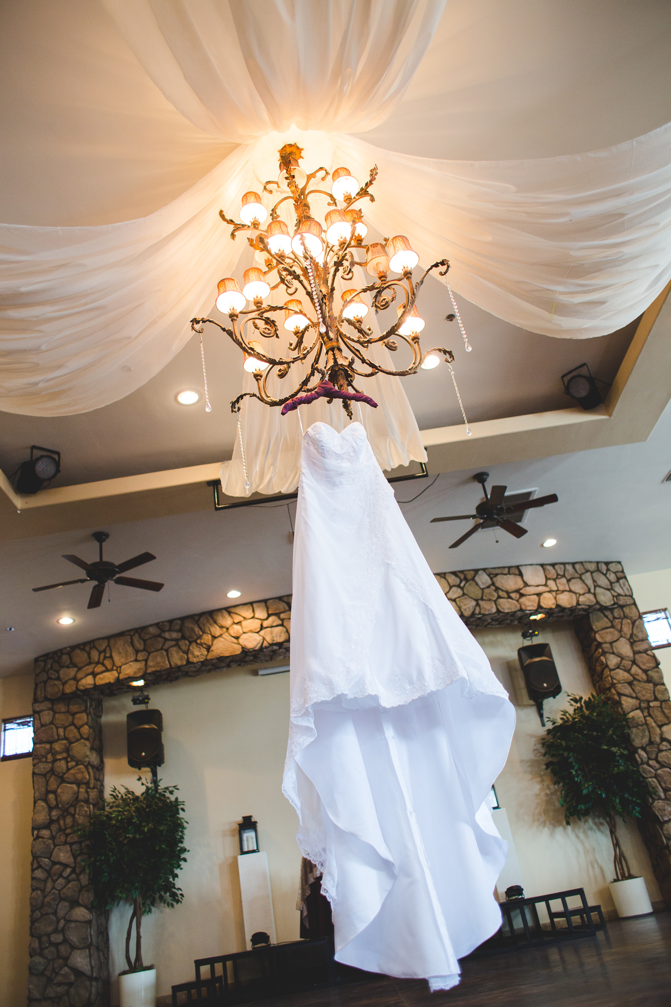 wedding dress detail shot hanging from chandelier mj