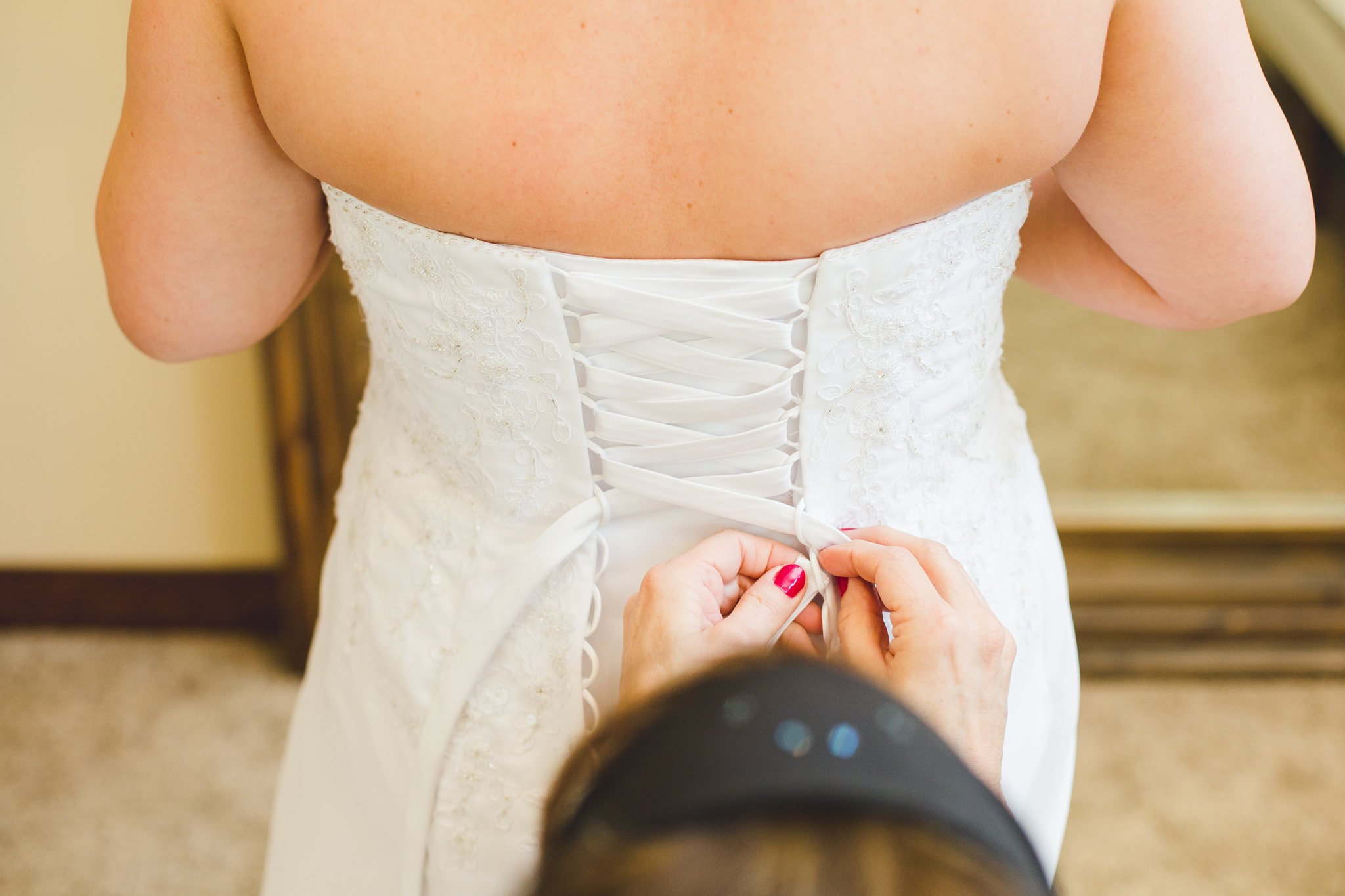 bride getting dress tied up mj