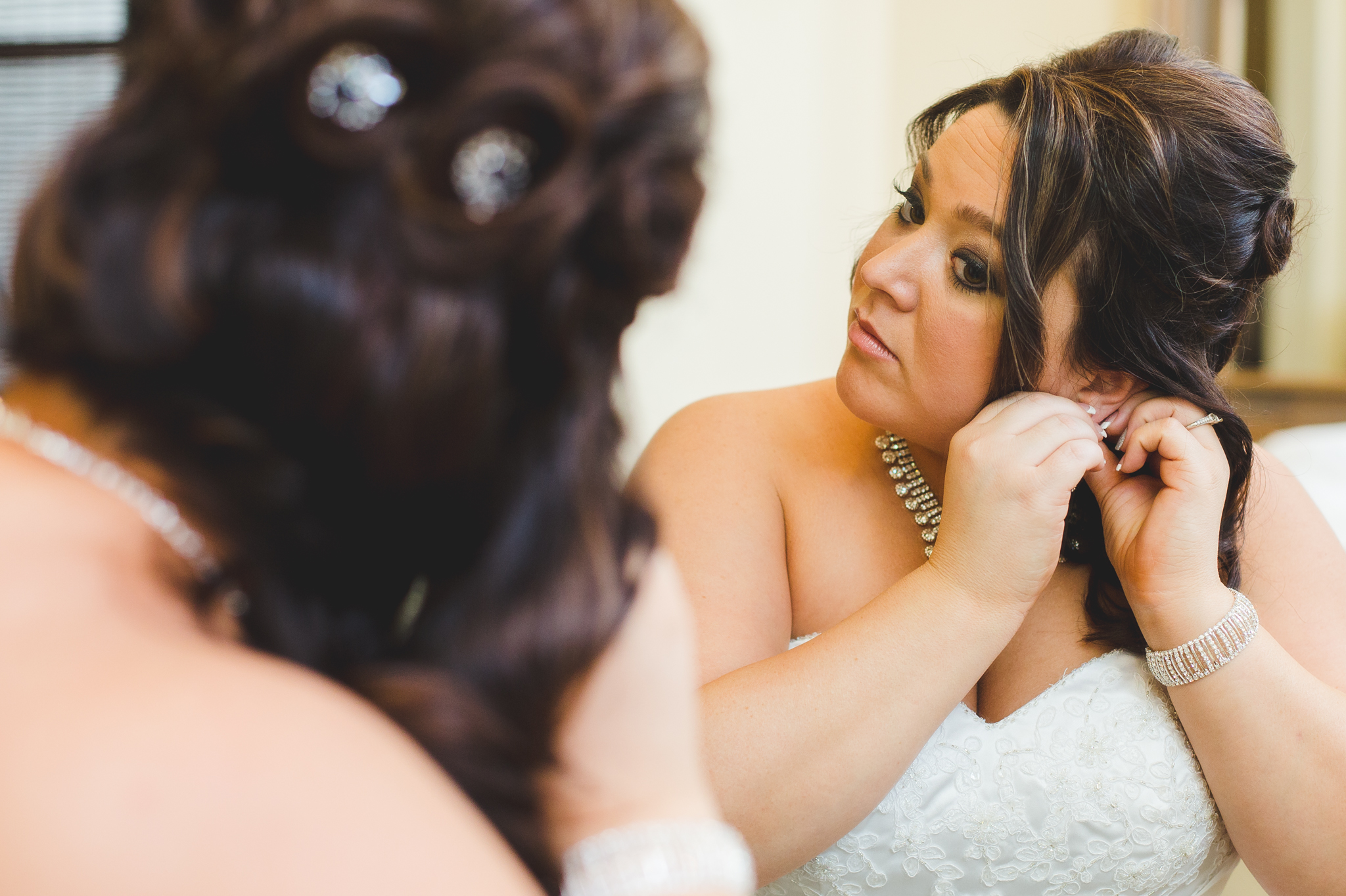 bride getting earrings on mj