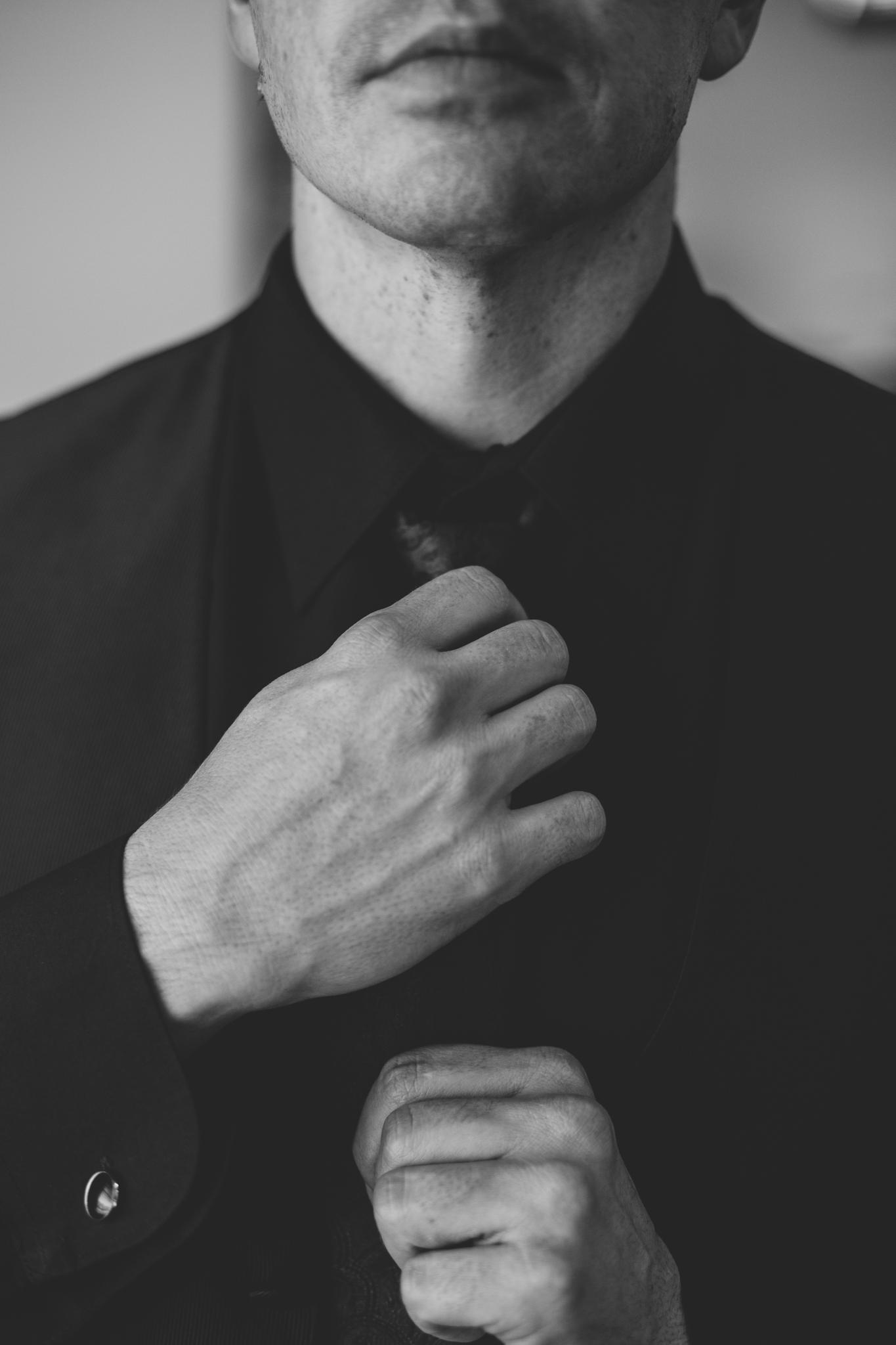 phoenix wedding photography bw groom putting tie on looks sharp mj