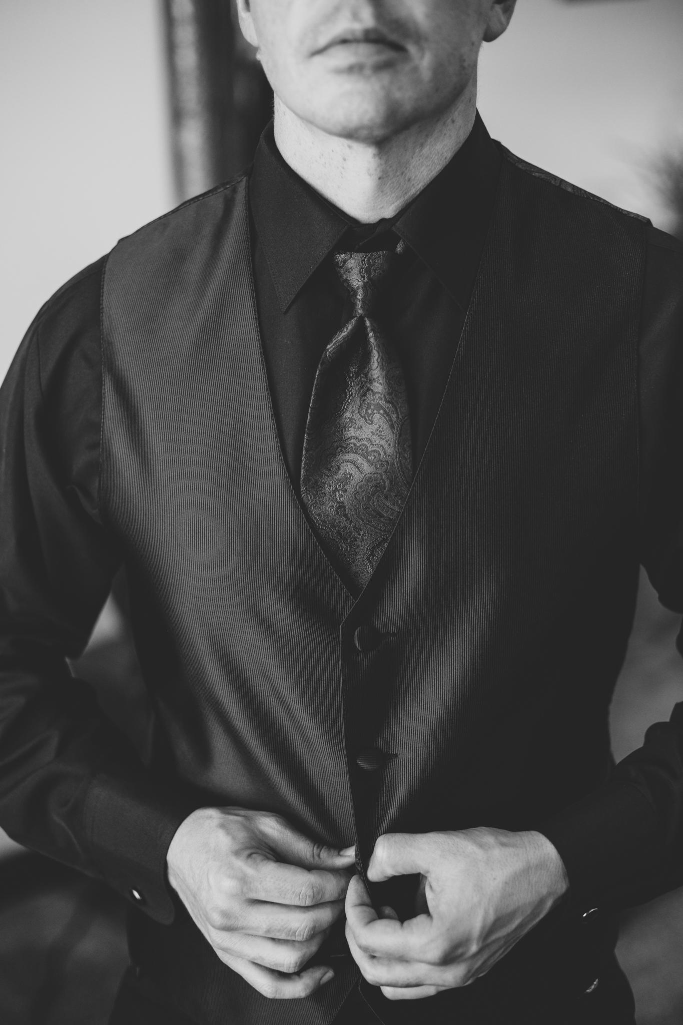 phoenix wedding photographer bw groom putting vest on mj