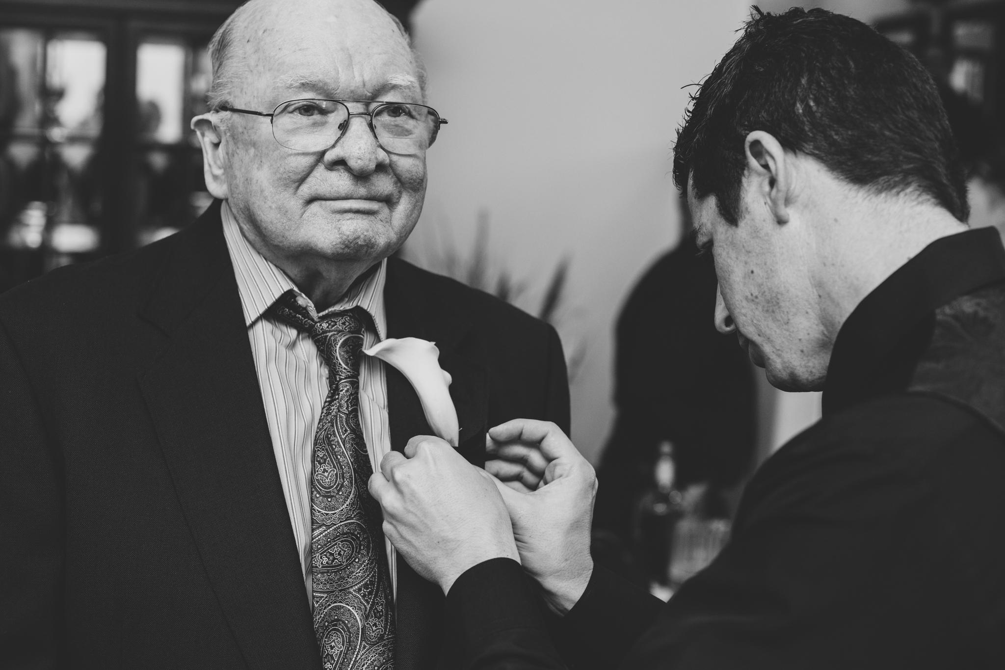 groom puts boutoniere on grandfather mj