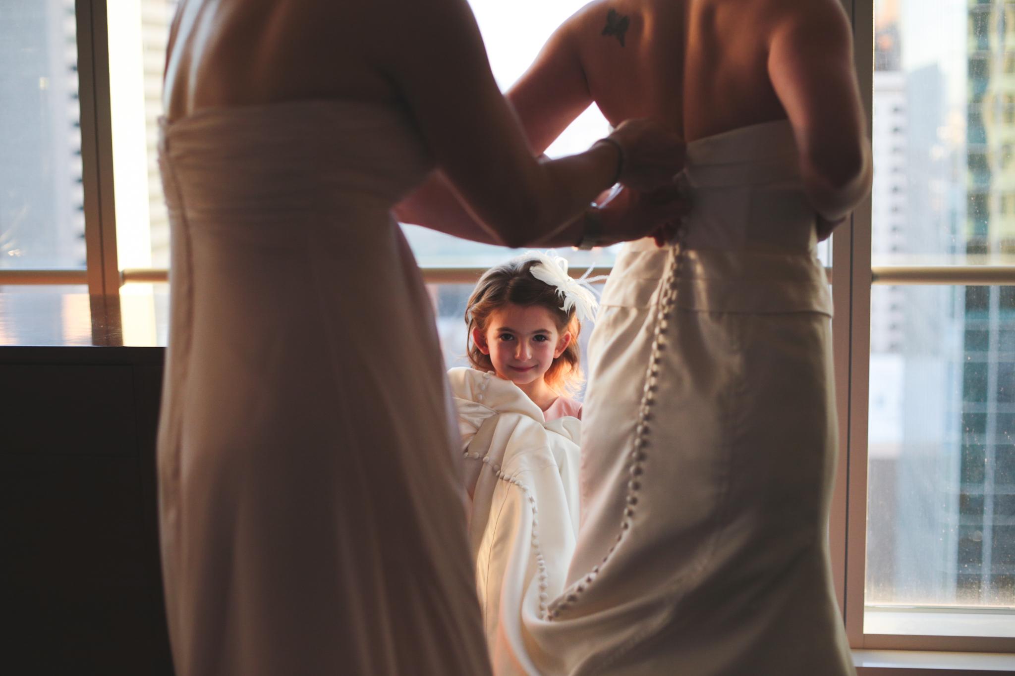 flower girl helps get dress on bride hj