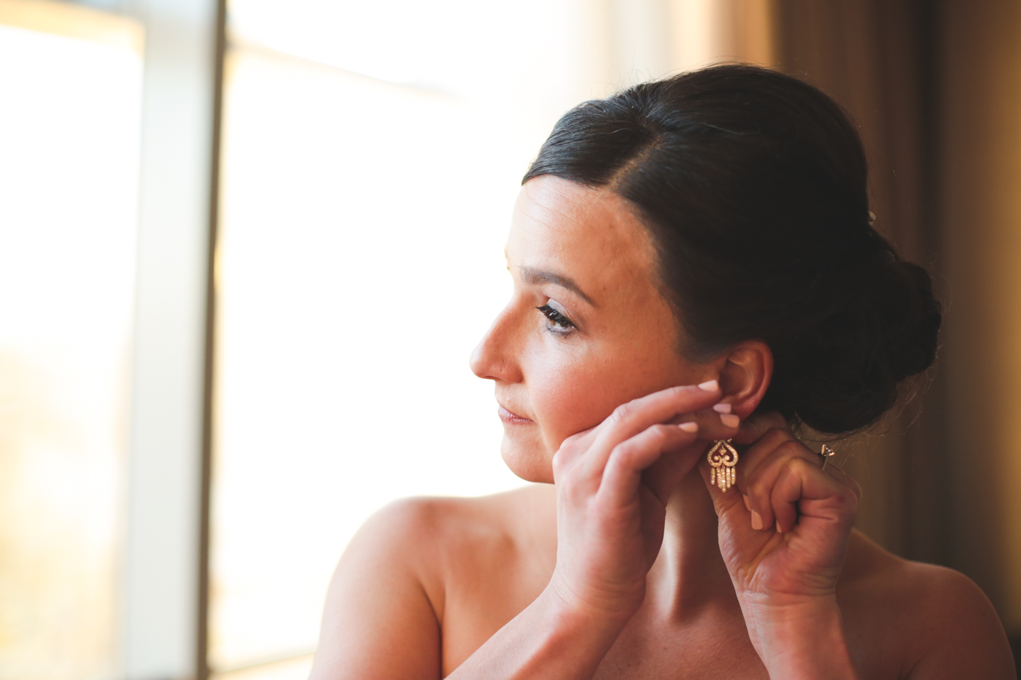 bride putting earrings on hj