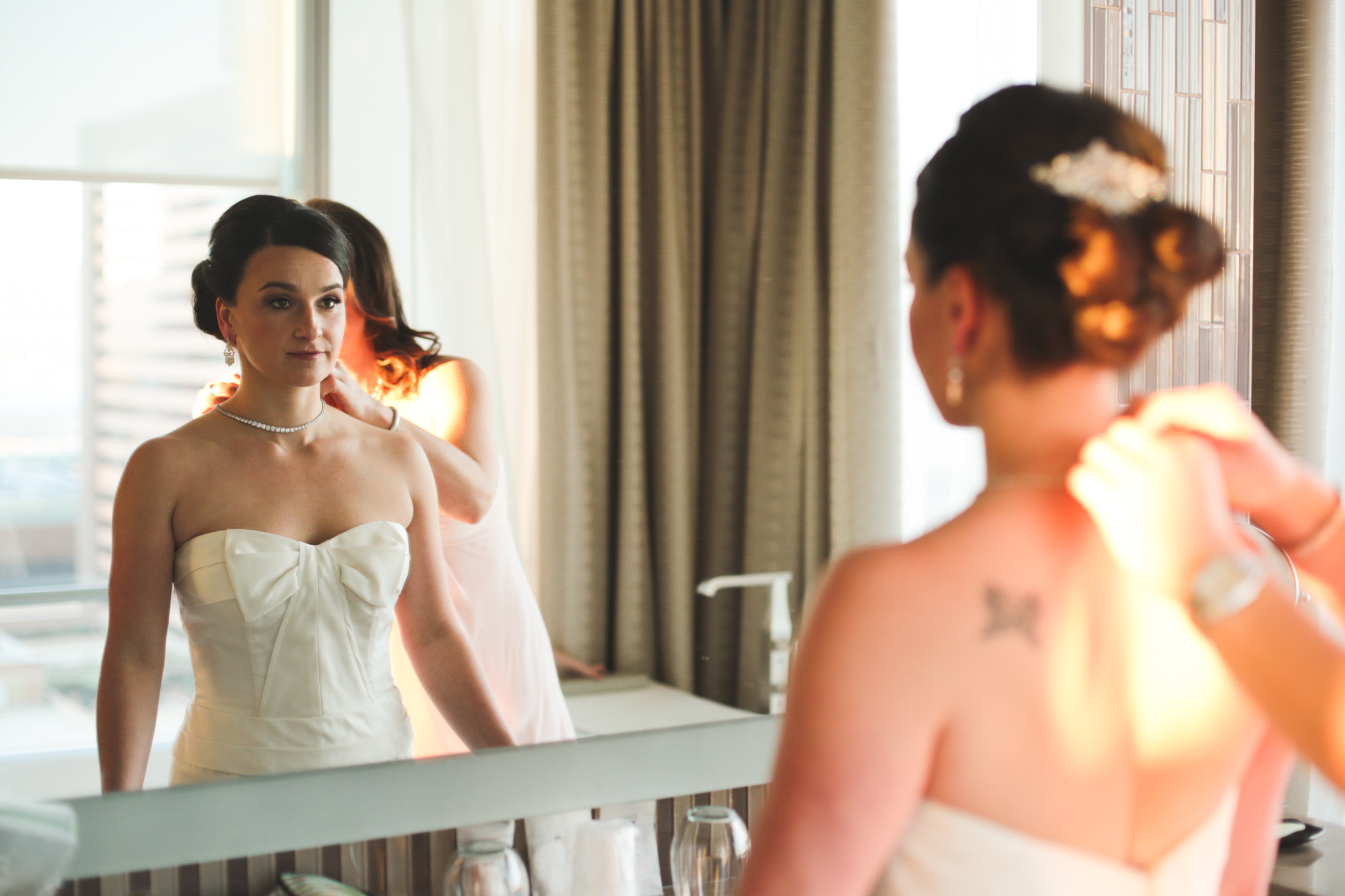 maid of honor puts necklace on bride hj