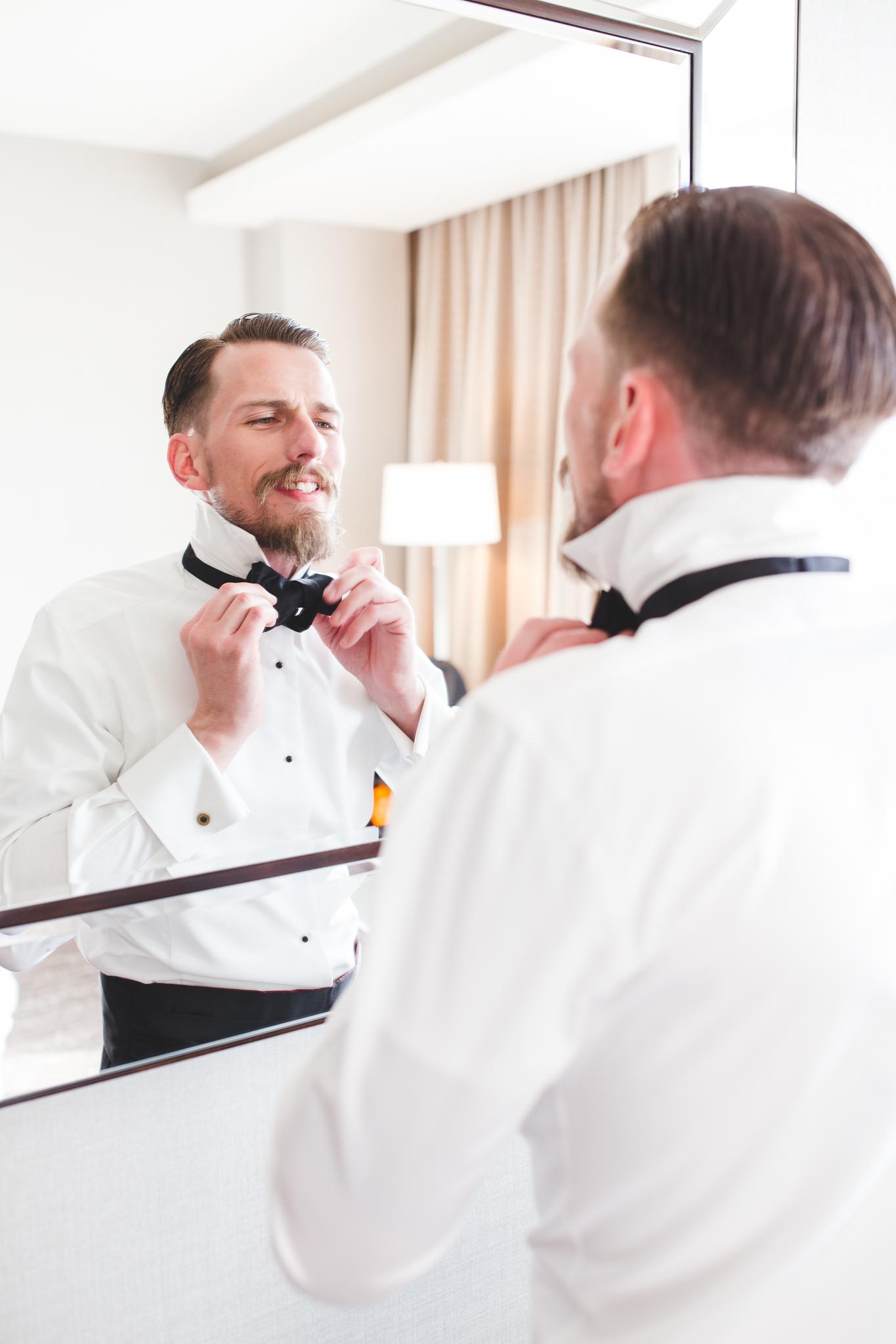 groom putting on bow tie hj