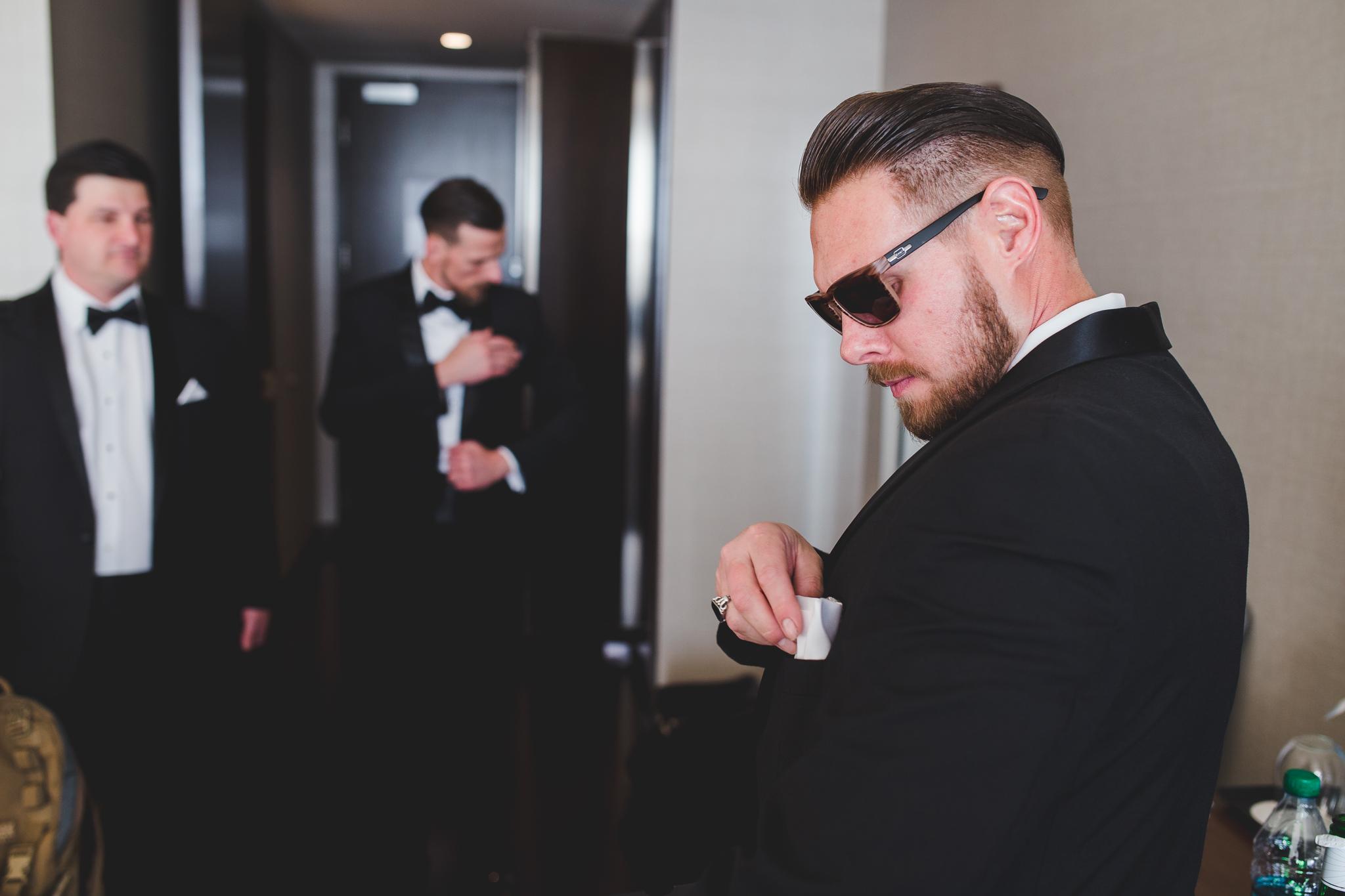groomsmen checks his pocket square hj