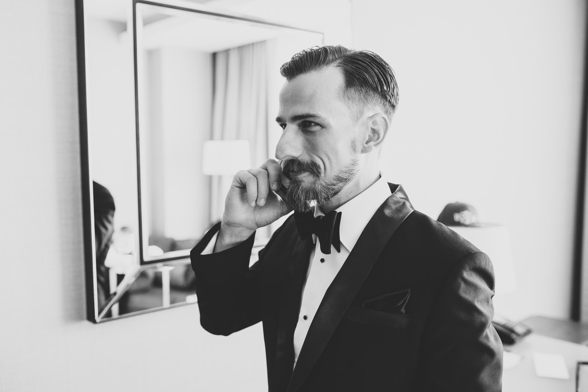 groomsmen on phone before wedding in tux hj