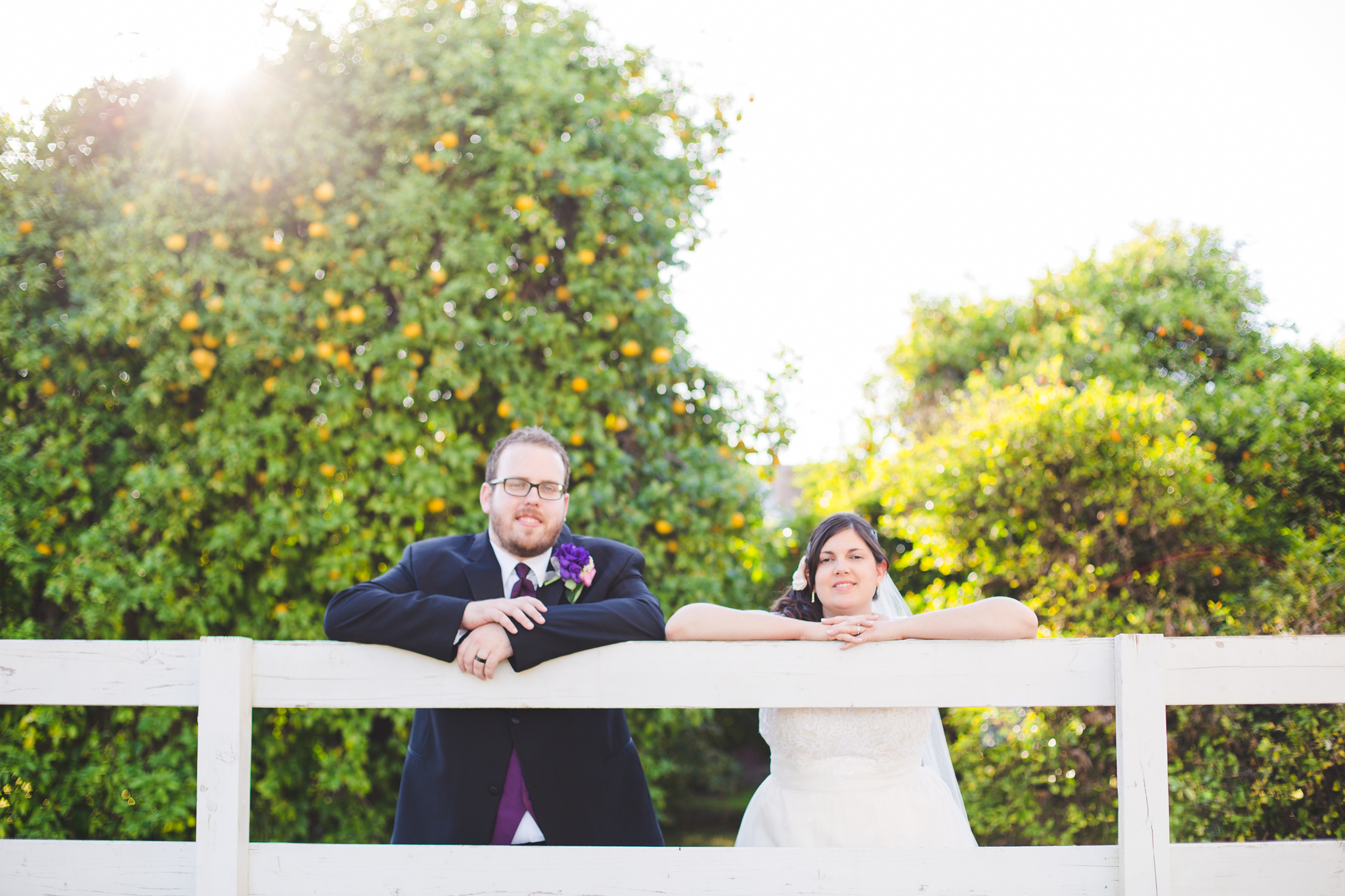 bride and groom stand along ranch fence sd