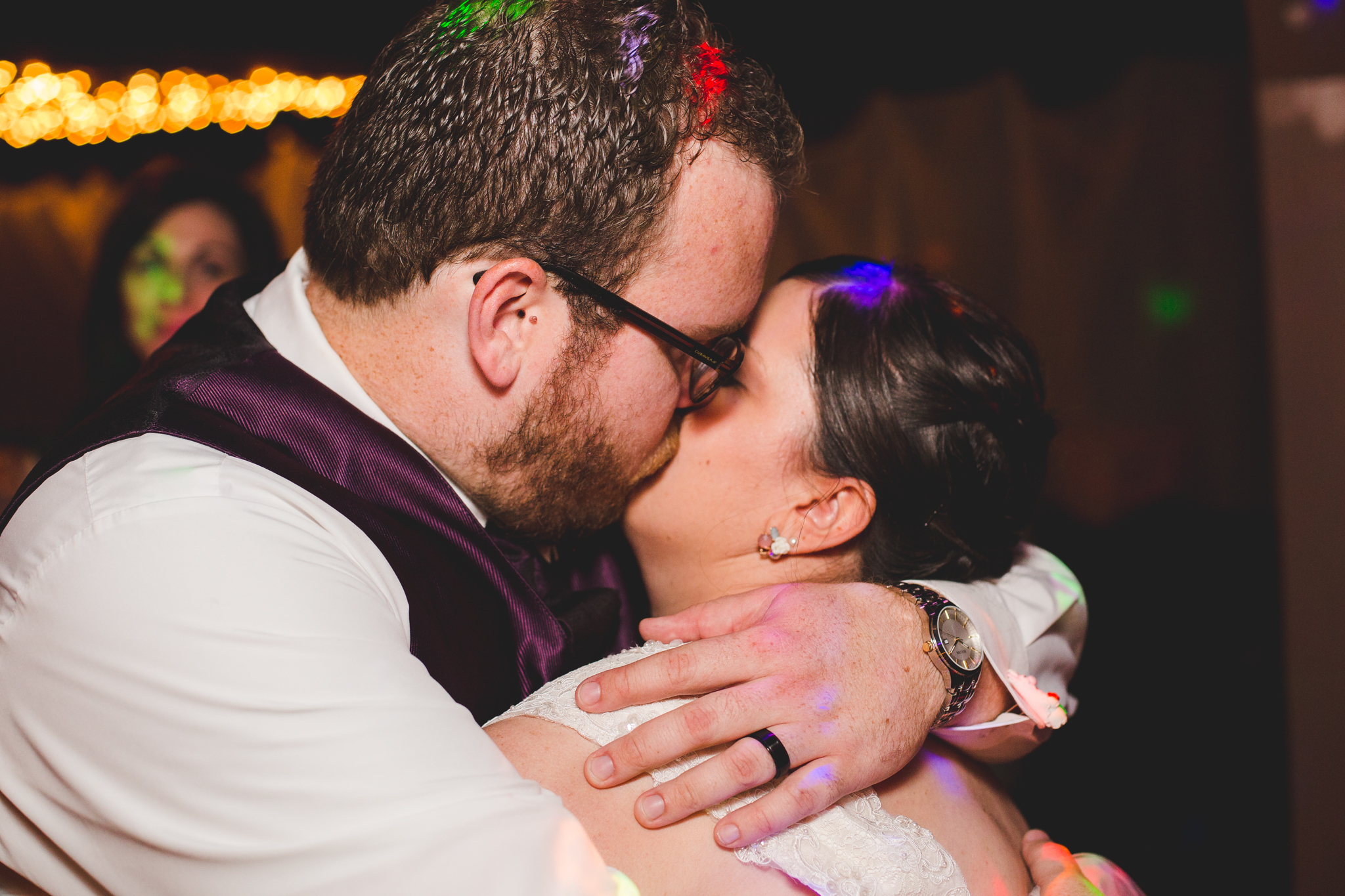 bride and groom kiss and embrace at reception sd