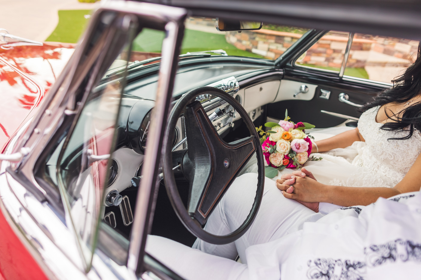 bride-and-groom-hold-hands-in-classic-car