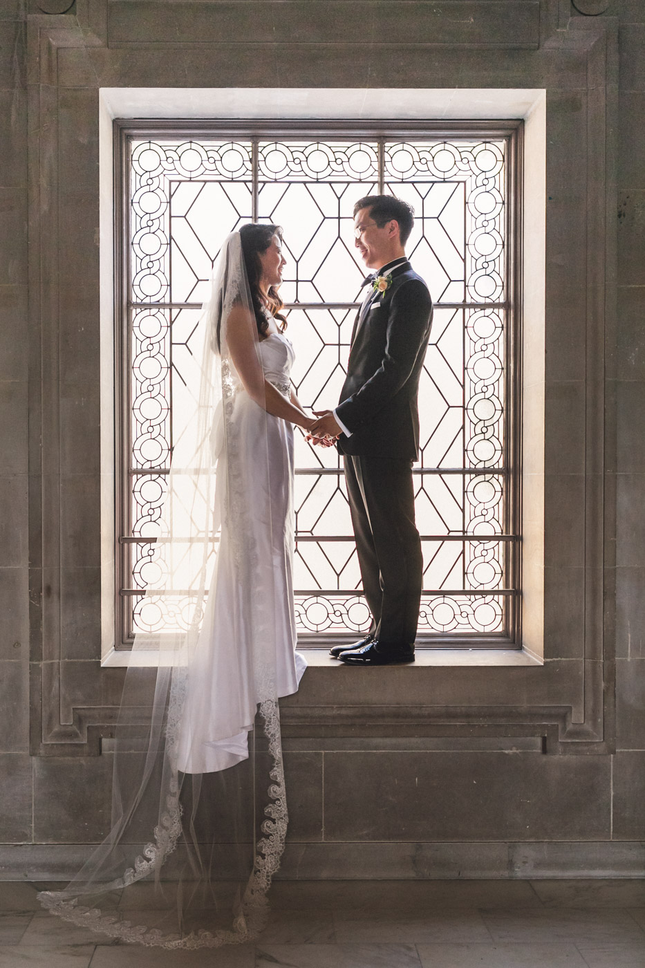 bride-and-groom-standing-in-window-san-francisco-city-hall