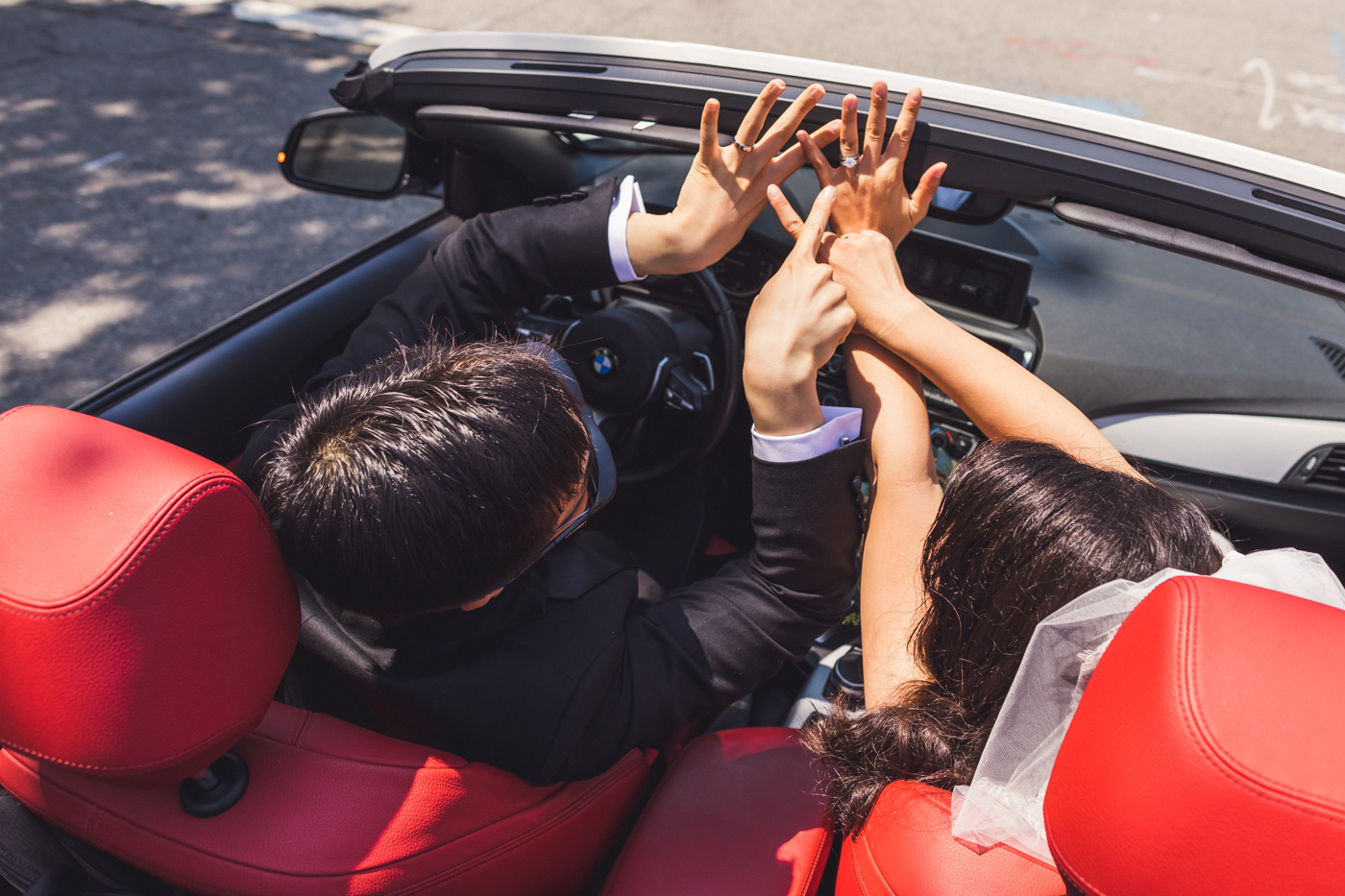bride-and-groom-showing-off-rings-in-convertible