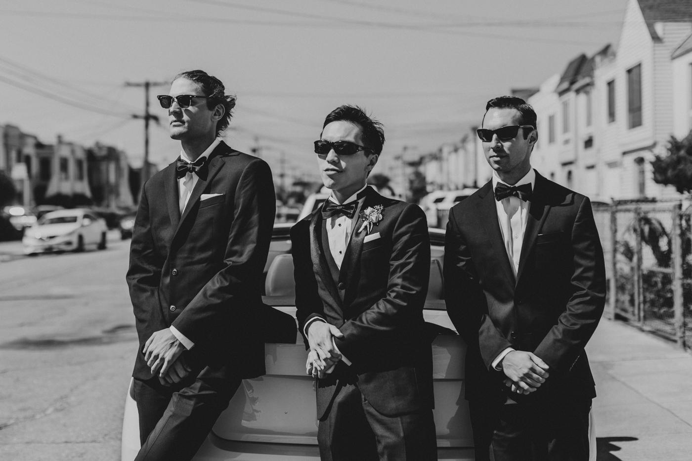 groom-and-groomsmen-leaning-on-car