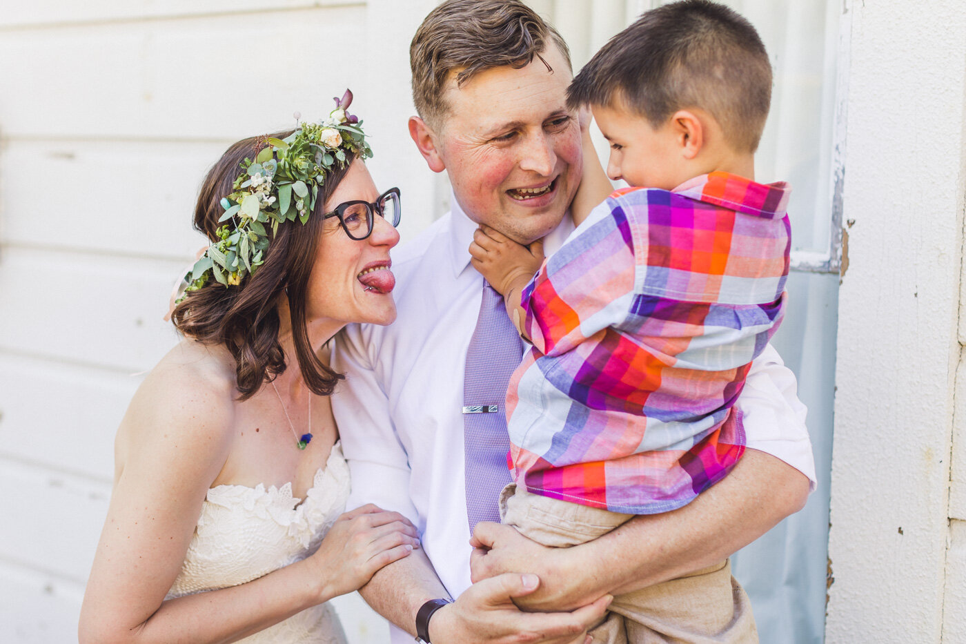 bride-and-groom-having-fun-with-child