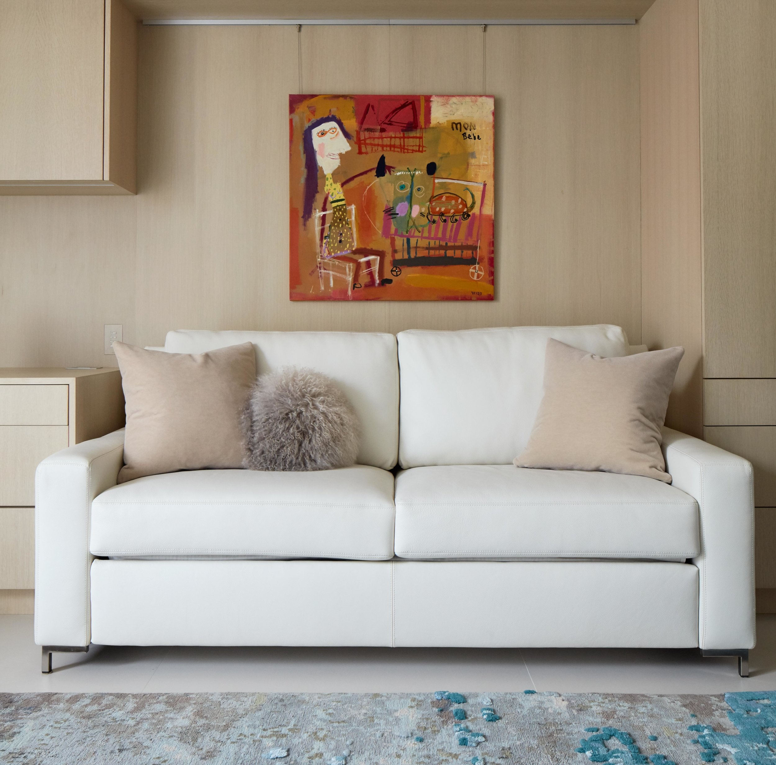 A painting by Vered Gersztenkorn hangs above a pullout sofa in the guest room