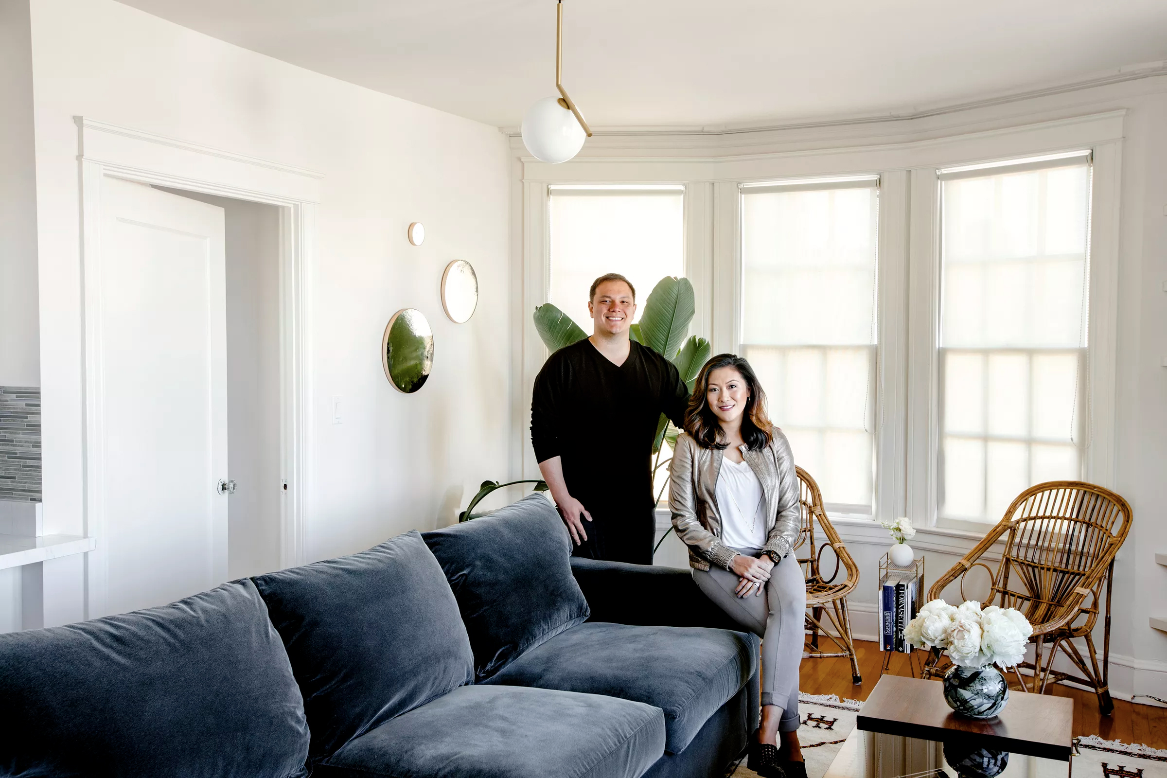 Niles Lichtenstein and Alicia Cheung Lichtenstein at home. When the couple got together, they opened a joint account to use for redecorating the apartment. The sofa is from  Crate & Barrel , the rattan chairs are from  Blue Ocean Traders , the coffee table is vintage and from  Donny O Antiques . The  Moon mirrors  are by artist Heather Palmer and the  1C pendant  from Flos by Michael Anastassiades.