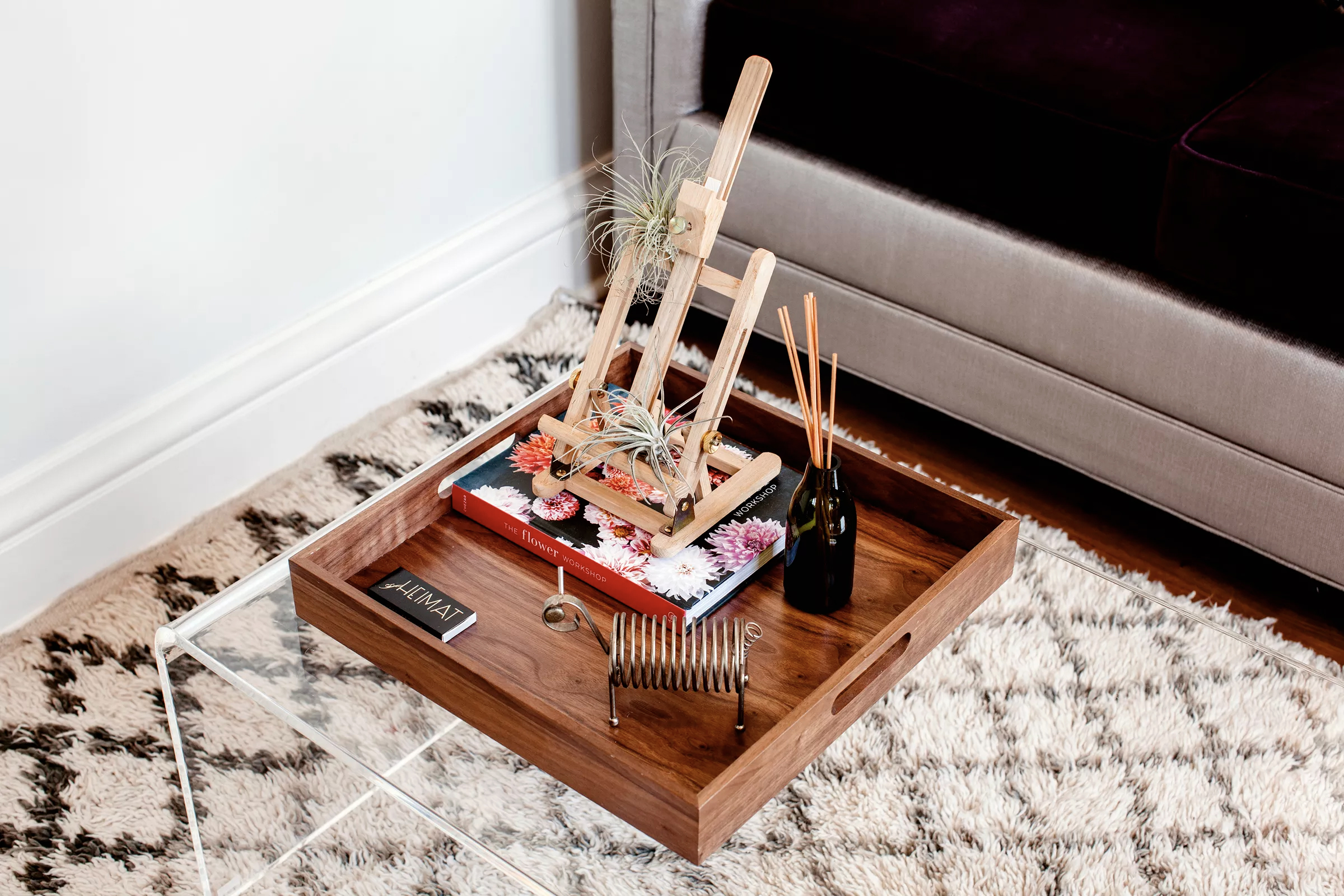 An acrylic  coffee table  from CB2 holds a tray that frames a small design vignette. The Moroccan rug is vintage.