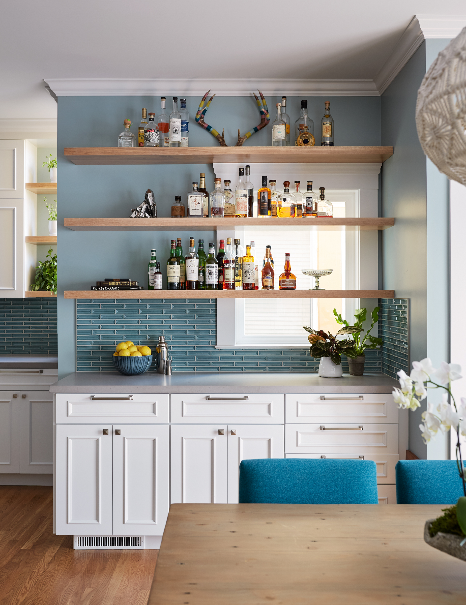 The Kitchen is painted in C2's Cadeau, the globe pendant lights are by Rejuvenation, the backsplash is in Global Tile Design's Half Baked, and the counters are Caesarstone in sleek concrete. Photography by John Merkl.