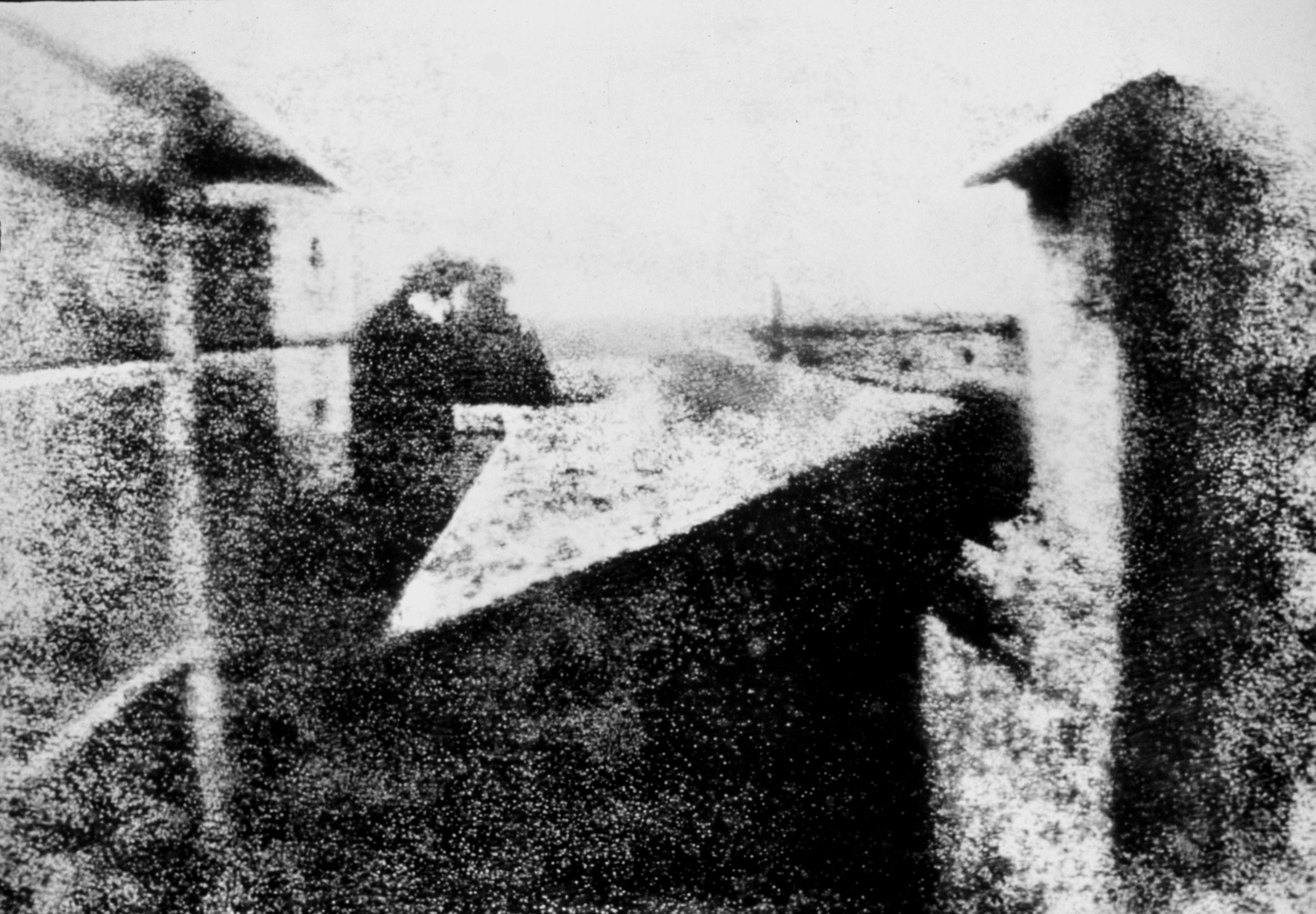 Das älteste erhaltene Foto, aufgenommen von Nicéphore Nièpce: Blick aus dem Arbeitszimmer in Le Gras, 20 x 25 cm. Durch die achtstündige Belichtungszeit erscheinen die Gebäude rechts und links sonnenbeschienen (Quelle: Wikimedia.org)