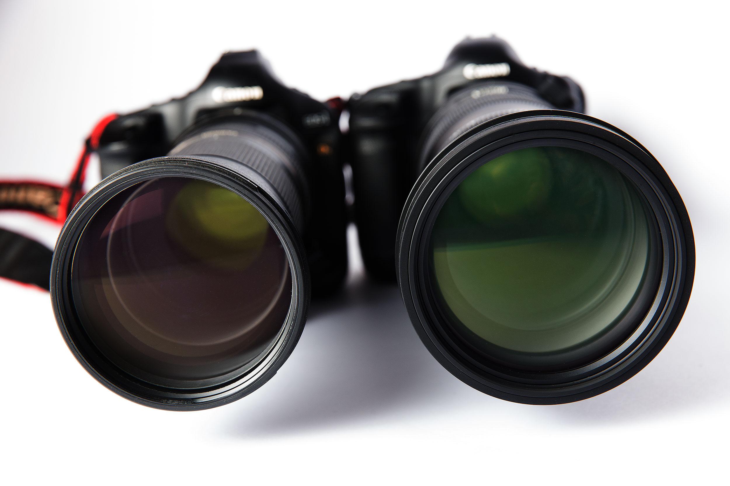 Ansicht der beiden Röhren von vorn: Das Tamron (links) hat einen Frontlinsendurchmesser von 95 mm, das Sigma 105 mm. Interessantes Details: Tamron liefert sein Zoom mit einer Kunststoff-Gegenlichtblende aus, Sigma legt seiner Röhre eine Metall-Gegenlichtblende bei.