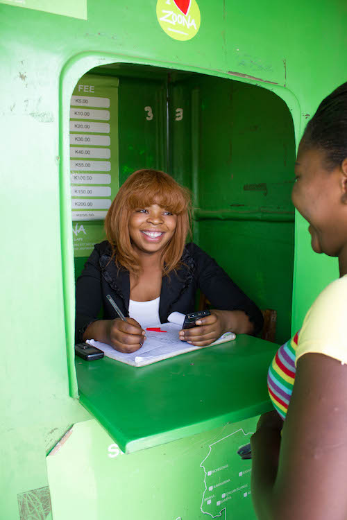 A Zoona teller recording a transaction at a booth