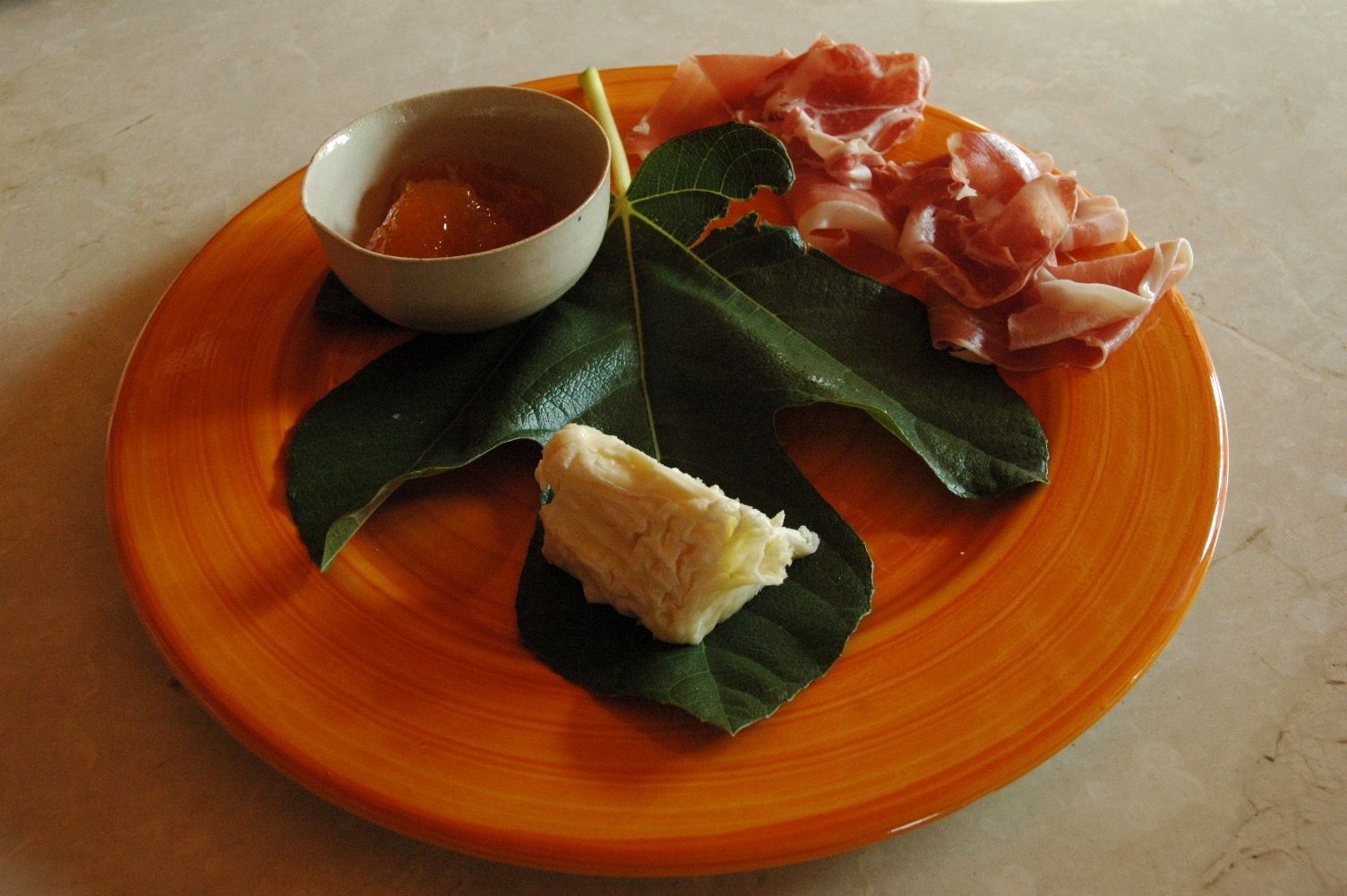 Goat cheese and prosciuttto served on a fig leaf with sweet onion jam