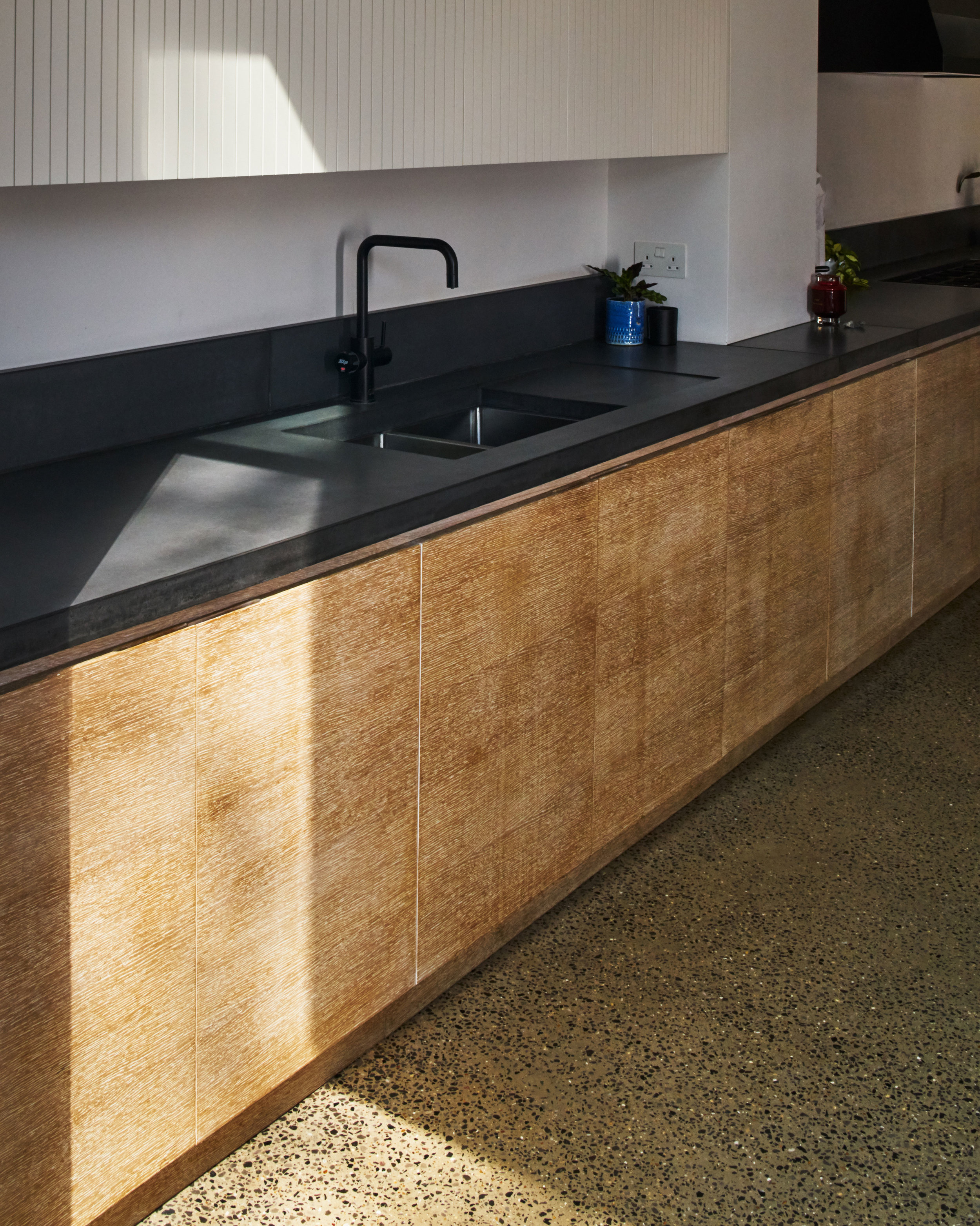 Black Corain work top with wooden kitchen cupboards