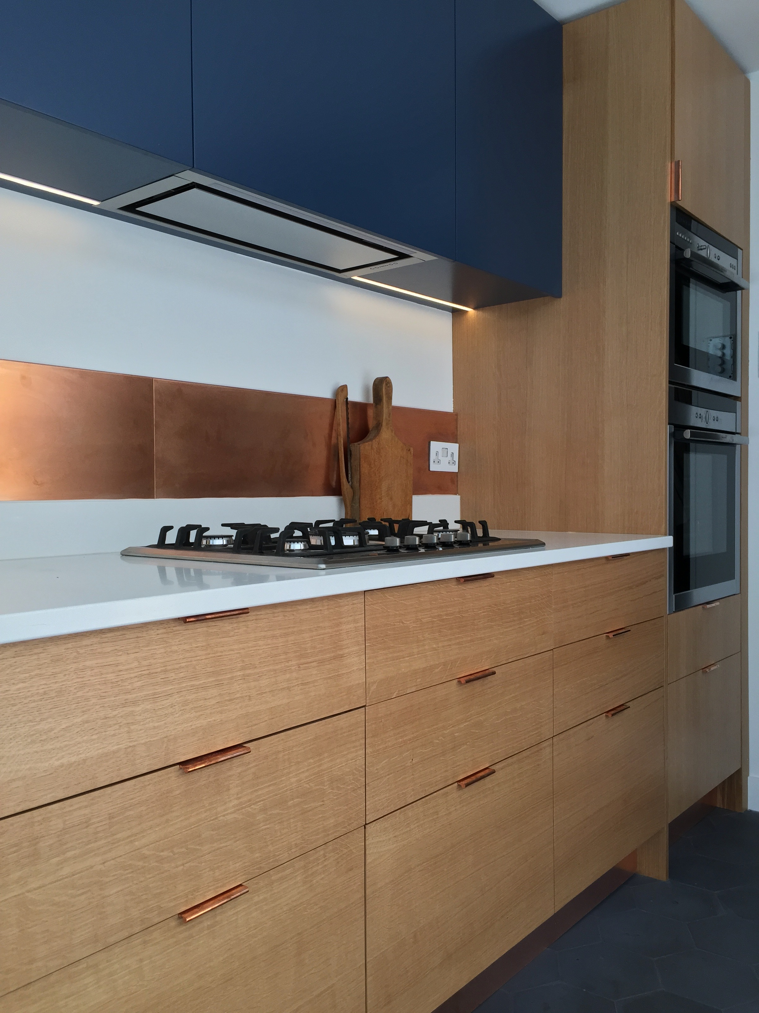 Cooper splashback with Blue cabinets and Spray Lacquered birch ply