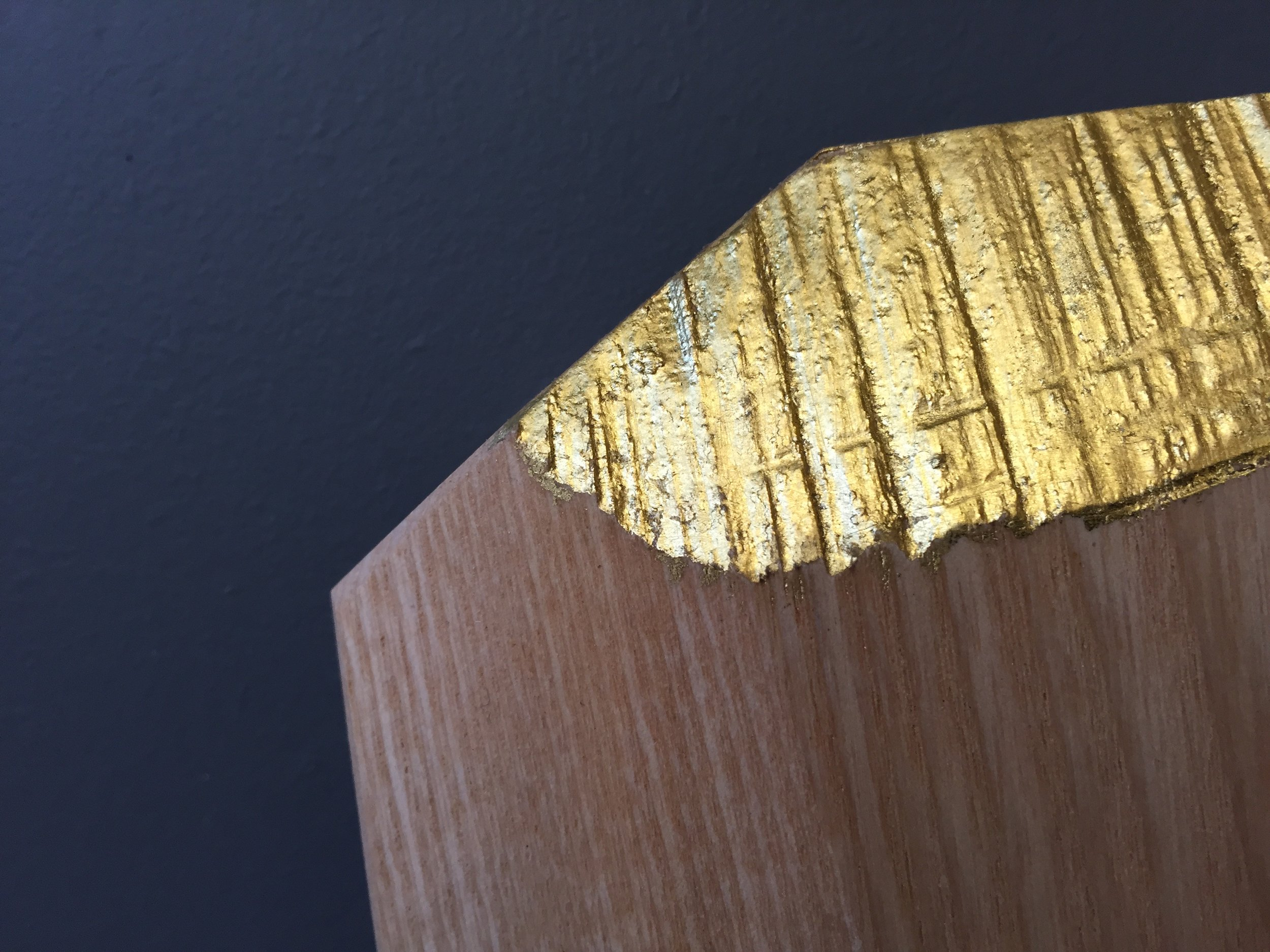 revealing a layer of 22 carat gold leaf on crafted clothes hangers