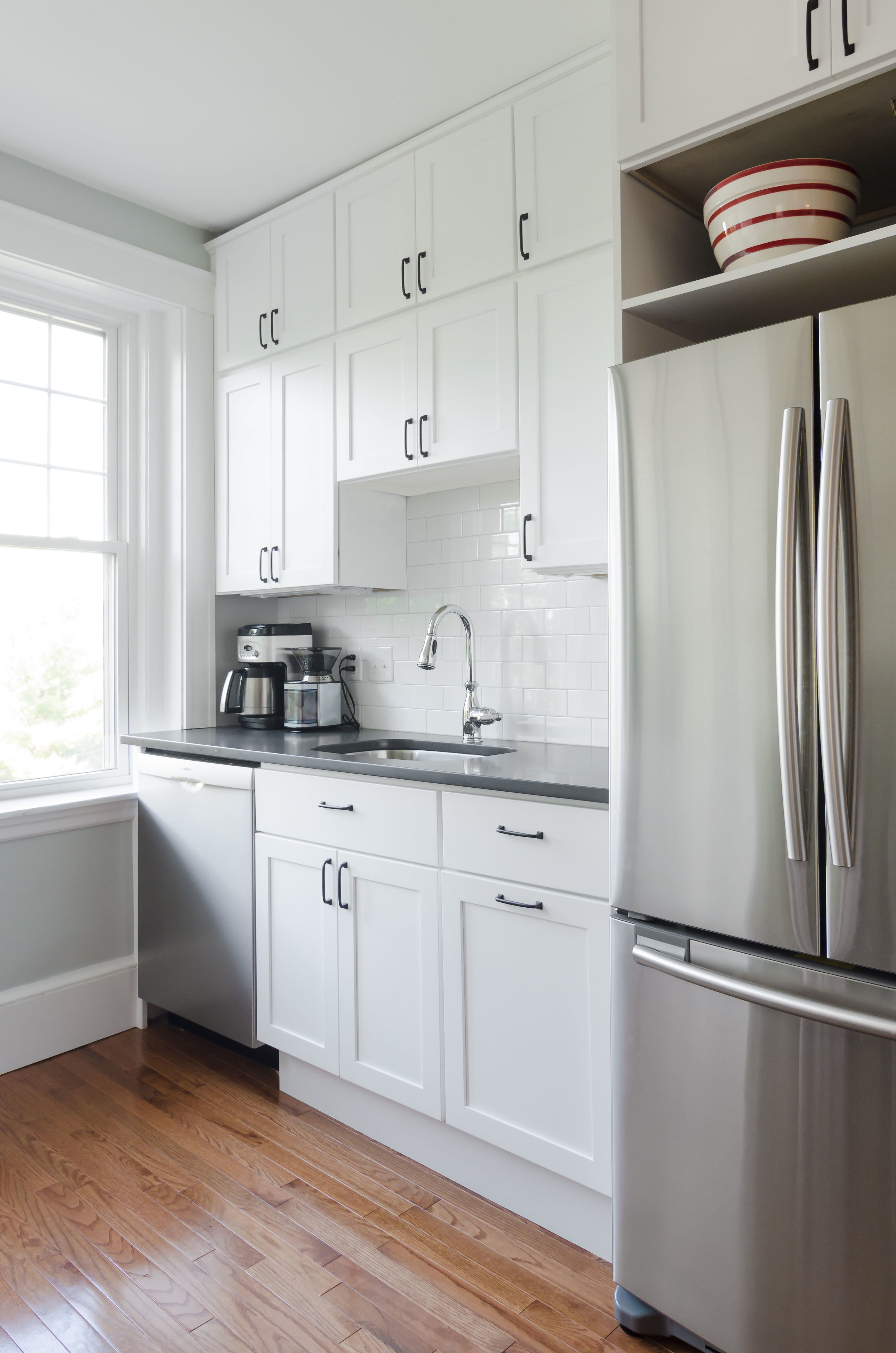 "Jamaica Plain, MA -- ""Sunny White"" Kitchen. A gut renovation and space reconfiguration, including new cabinets, counters, tile backsplash, plumbing, lighting and flooring. A narrow, separate pantry was removed to create an airy workspace and storage. Design by the homeowner and Bailey•Davol•Studio•Build."