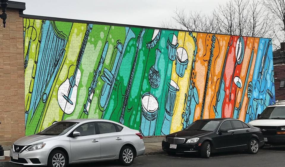 """This rendering by Franklin Marval was selected by our Public Art Design subcommittee and property owner Richard Cohen to be painted on his building at 199 Concord Street. The mural will face north and welcome drivers on Concord Street into our vibrant downtown business district.   Want to stay up to date with the mural's progress? Visit our webpage, """"Marval's Musical Mural,"""" for updates and photos of the progress."""