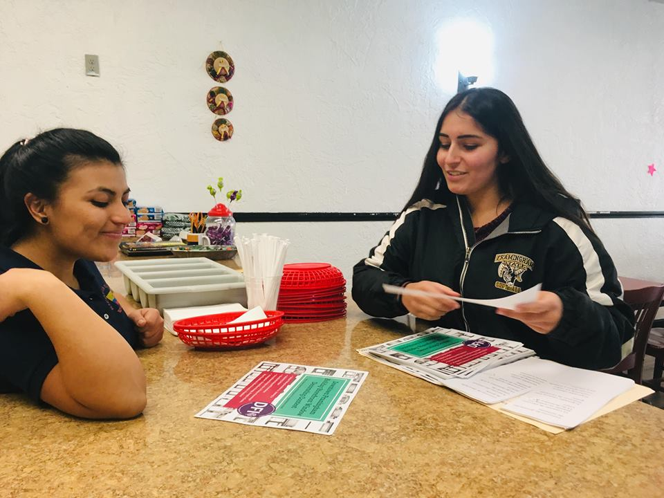 Kelsi Gunarathne, the DFI Cultural Projects Manager, speaks to the manager of Rincon La Cabana about the Holiday Storefront Window Decorating Contest