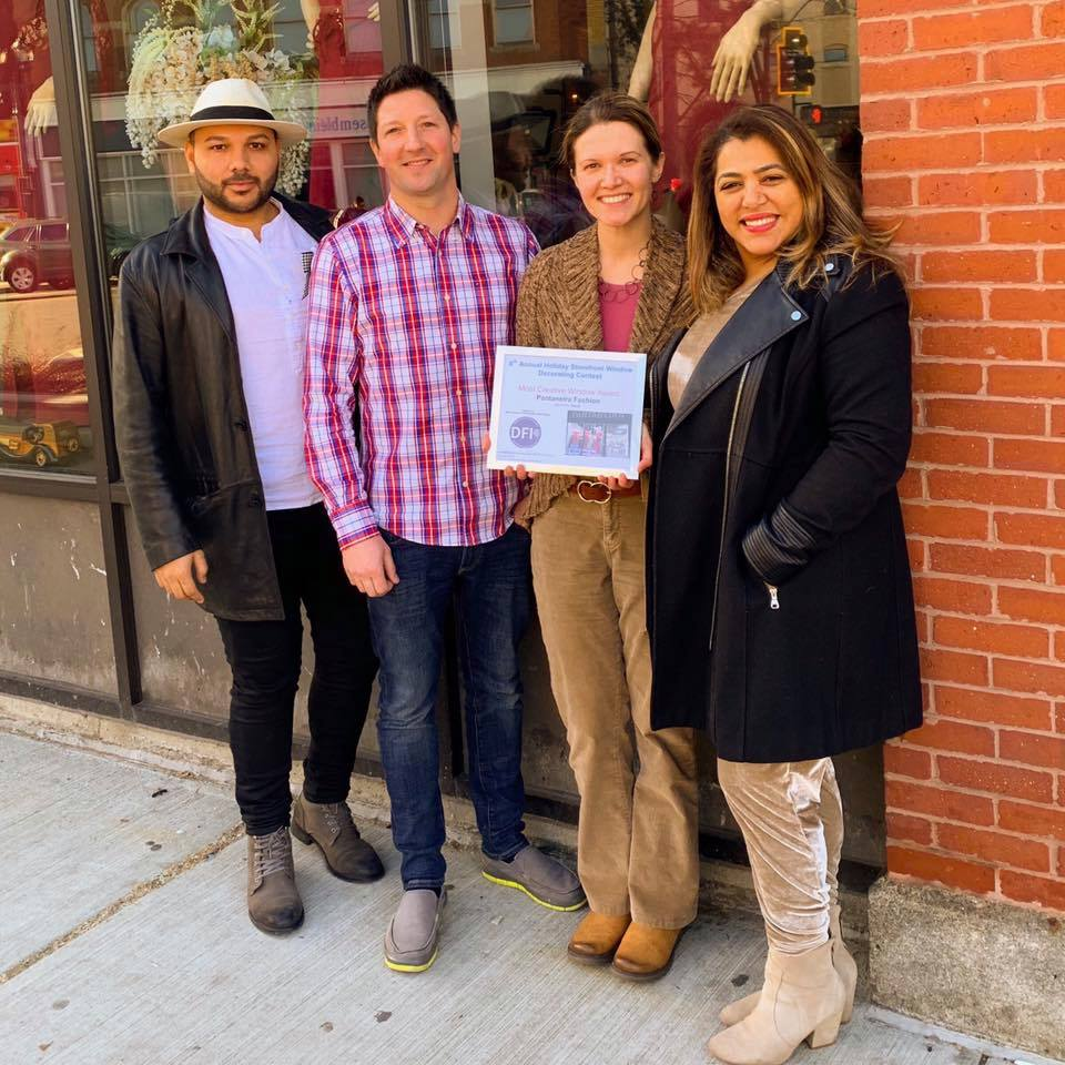 Don Cavicchi (center left), owner of Cav Audio and Video Design, presents the  Most Creative Storefront Award  to Vanderleia Sales (right), owner of  Pantaneira Fashion .