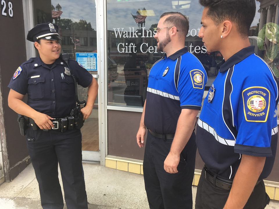 Framingham Police Officer Kat Demoraes (left) greets Adam Fini (center) and Gabriel Araujo (right) of the Downtown Engagement Team as they cross paths near City Hall.